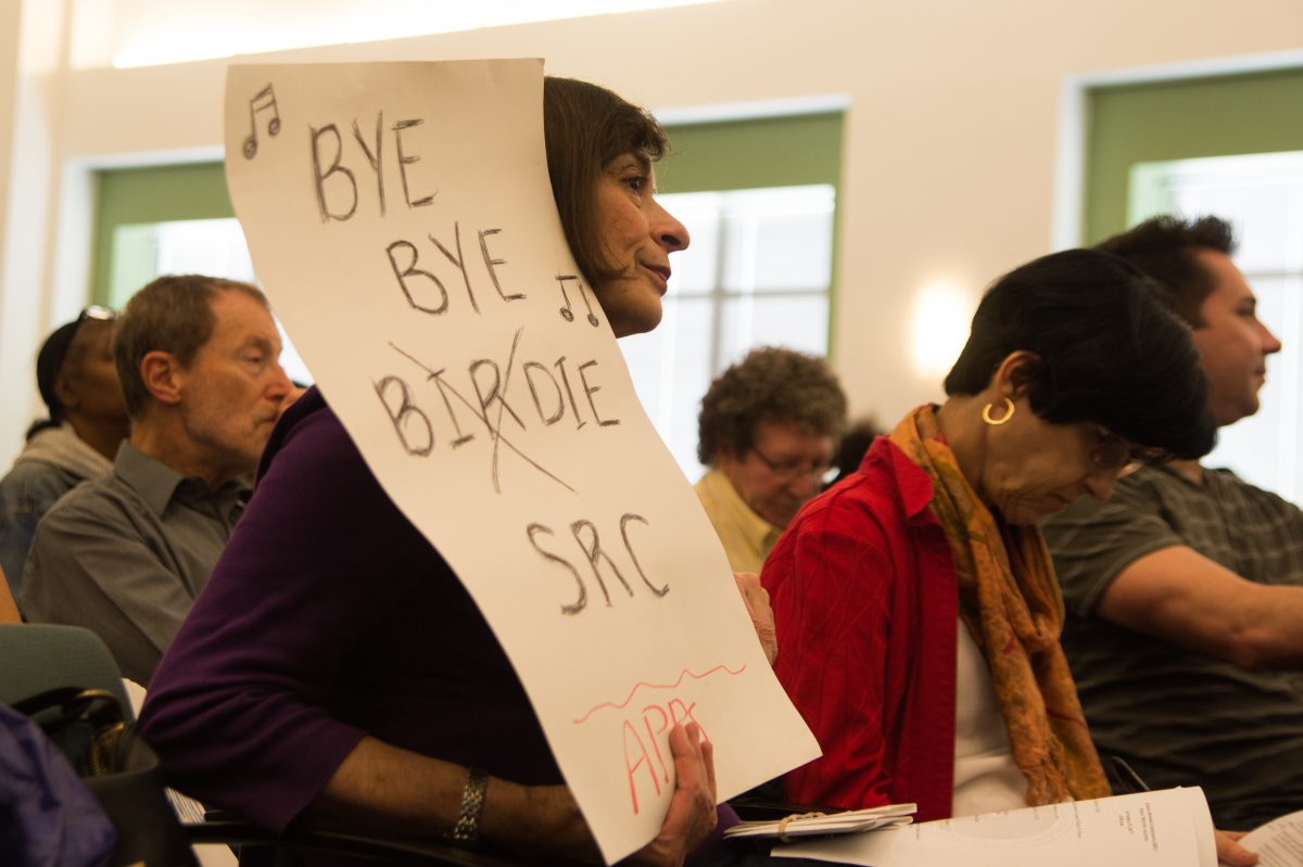 Ilene Poses holds a sign at the SRC meeting Thursday calling for the SRC to be disbanned.