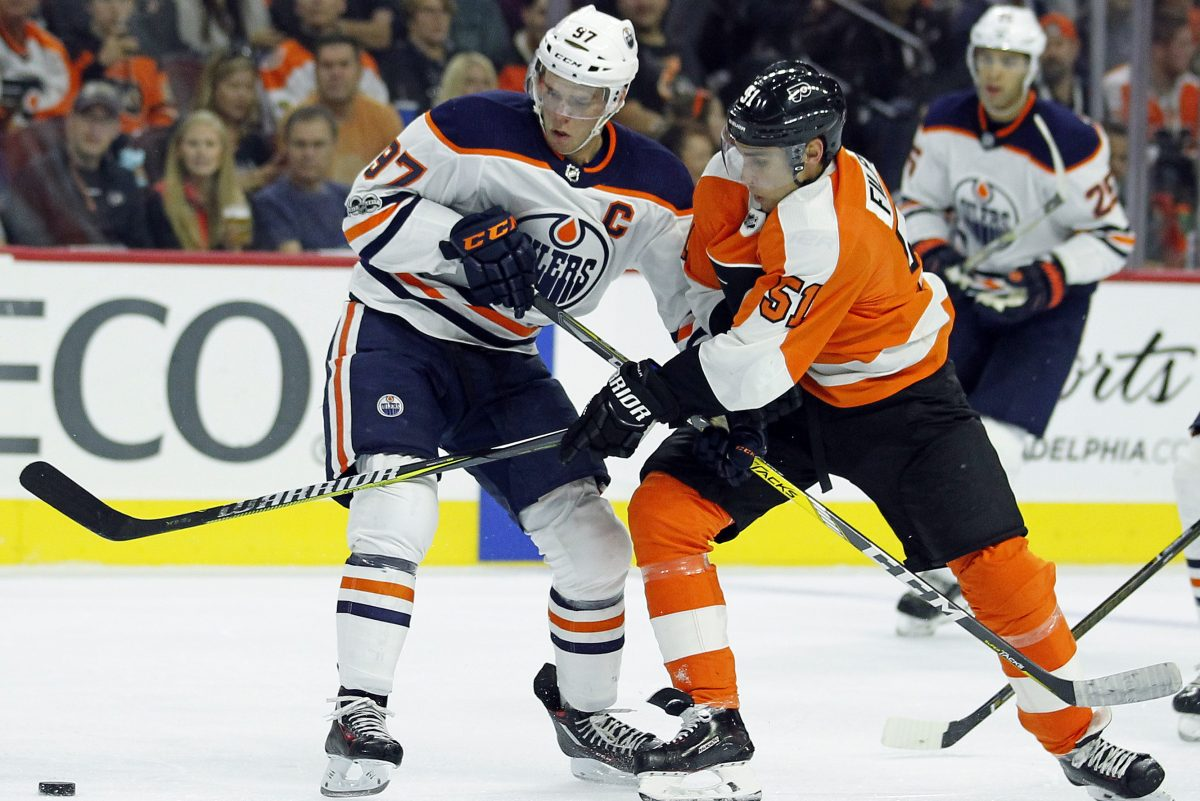 Oilers' center Connor McDavid, left, and Flyers' center Valtteri Filppula move to the loose puck during the second period.