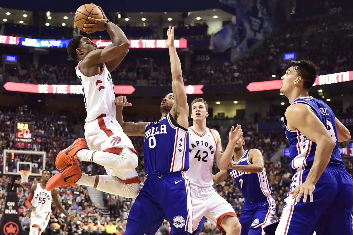 Raptors guard DeMar DeRozan (left) shoots over 76ers guard Jerryd Bayless (0) as Raptors center Jakob Poeltl (42) and 76ers forward Dario Saric (right) look on.