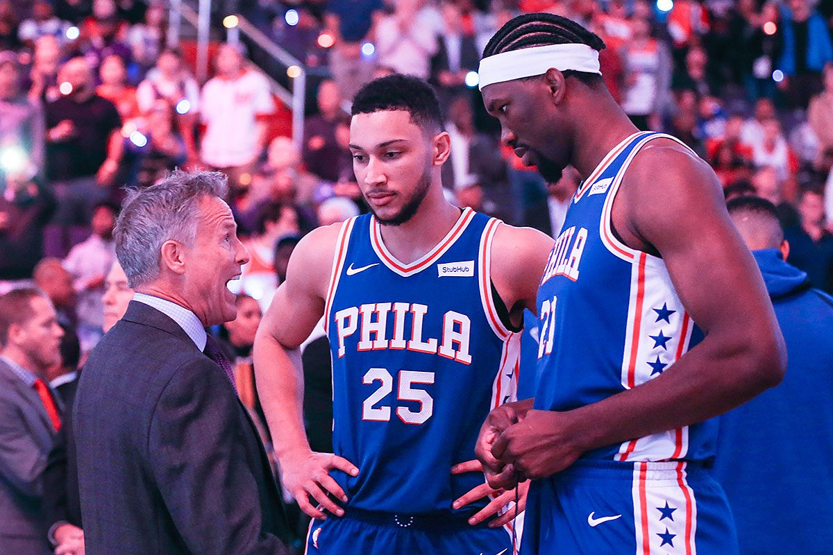 The Philadelphia 76ers' Brett Brown talks with Ben Simmons (25) and Joel Embiid, right, before action against the Washington Wizards at the Capital One Arena in Washington, D.C., on Wednesday, Oct. 18, 2017. The Wizards won, 120-115.