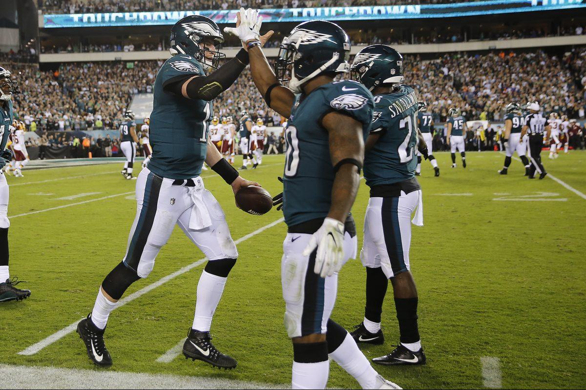 Eagles' quarterback Carson Wentz, left, celebrates a second-quarter touchdown with Corey Clement (center) and Wendell Smallwood.