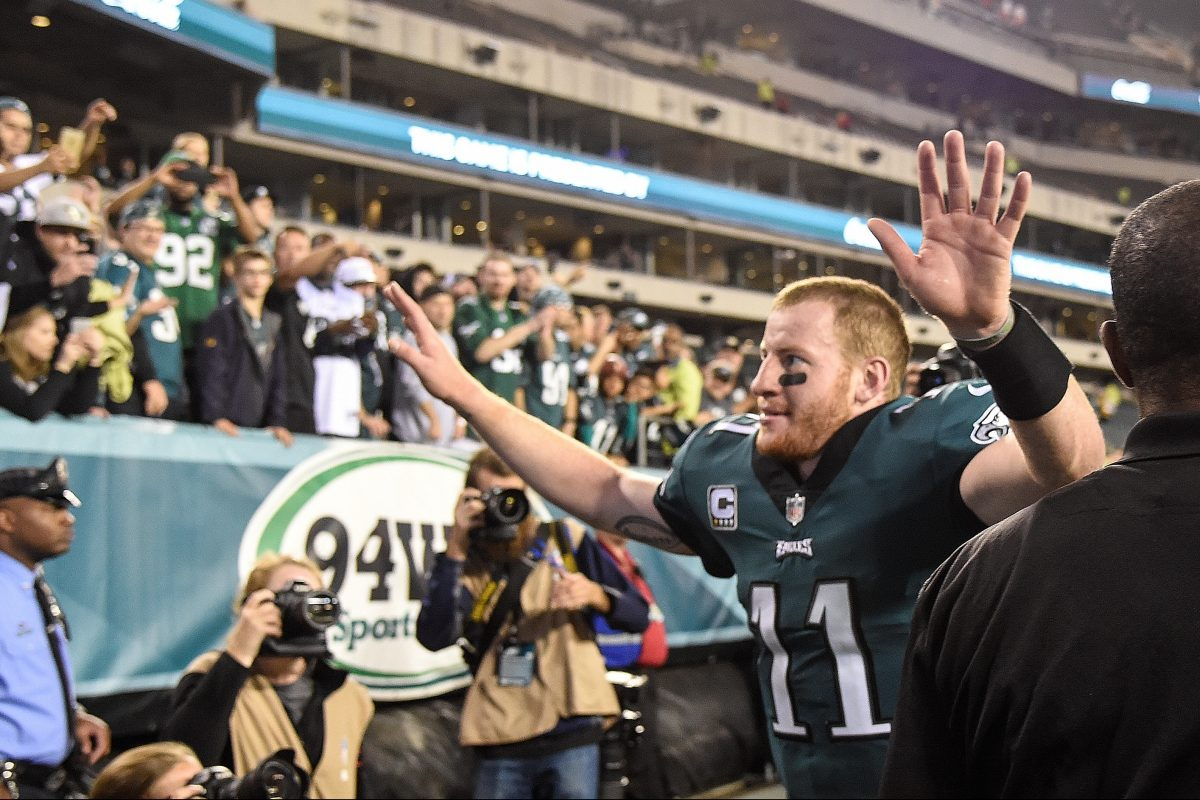 Eagles quarterback Carson Wentz waves his arms to the fans as he leaves the field after the Eagles beat the Washington Redskins, 34-24, at Lincoln Financial Field.