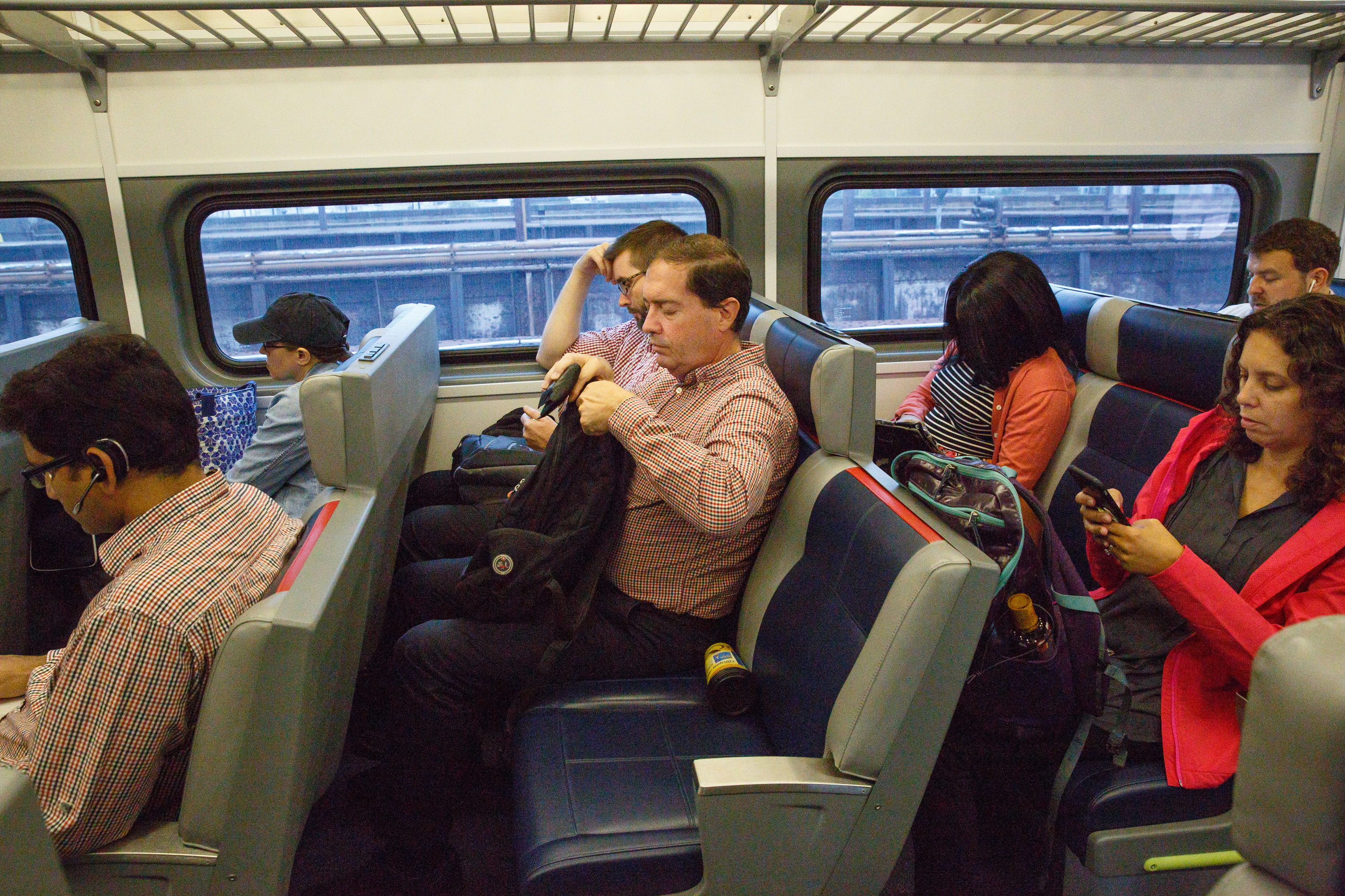 Matthew White, center, prepares to exit the train during his morning commute from Malvern to Suburban Station on Oct. 11. JESSICA GRIFFIN / Staff Photographer