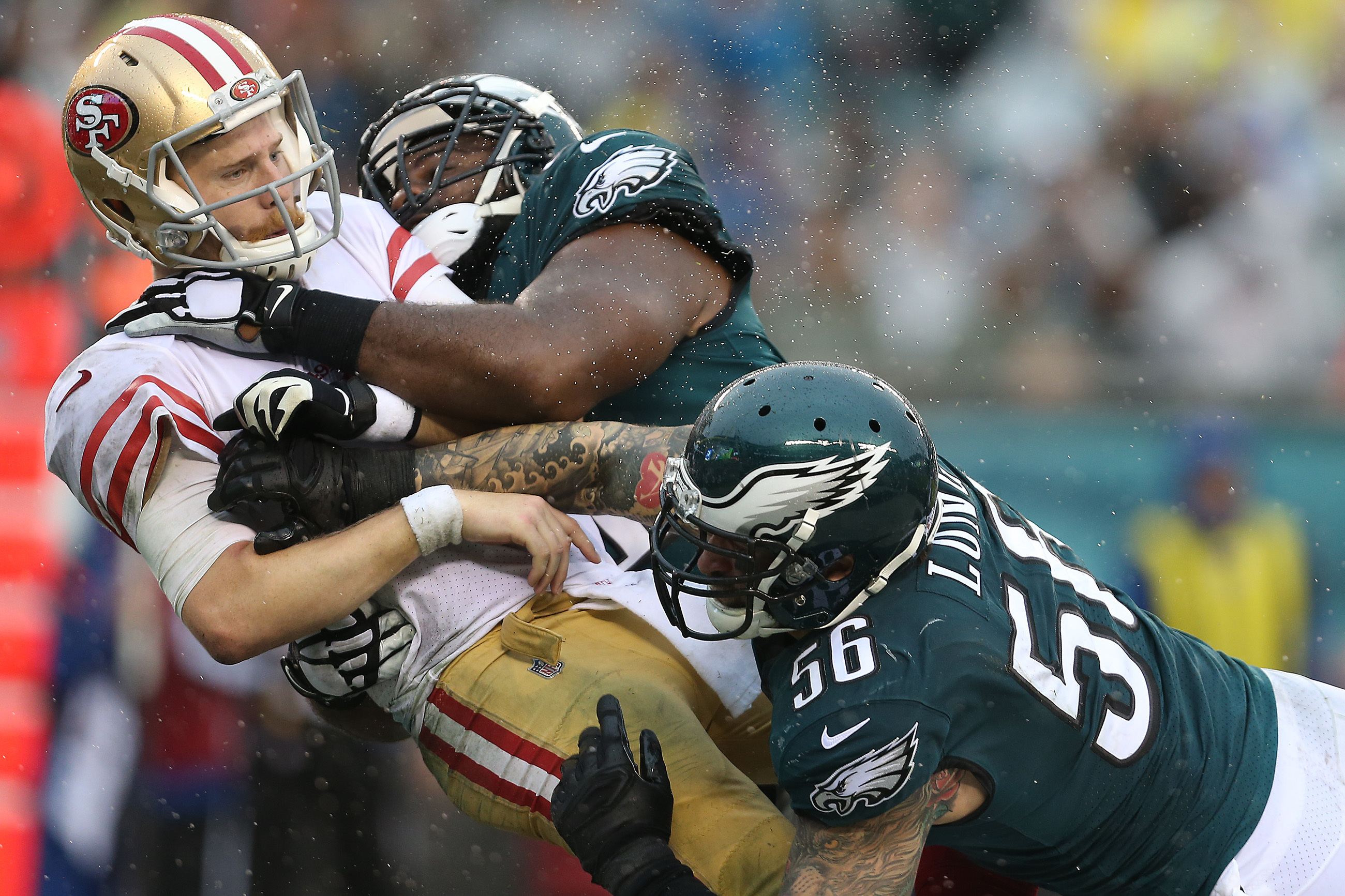 49ers' quarterback C.J. Beathard, left, is hit by the Eagles' Fletcher Cox, center, and Chris Long, right, after releasing the ball in the 3rd quarter. Philadelphia Eagles win 33-10 over the San Francisco 49ers in Philadelphia, PA on October 29, 2017. The pass fell incomplete. DAVID MAIALETTI / Staff Photographer