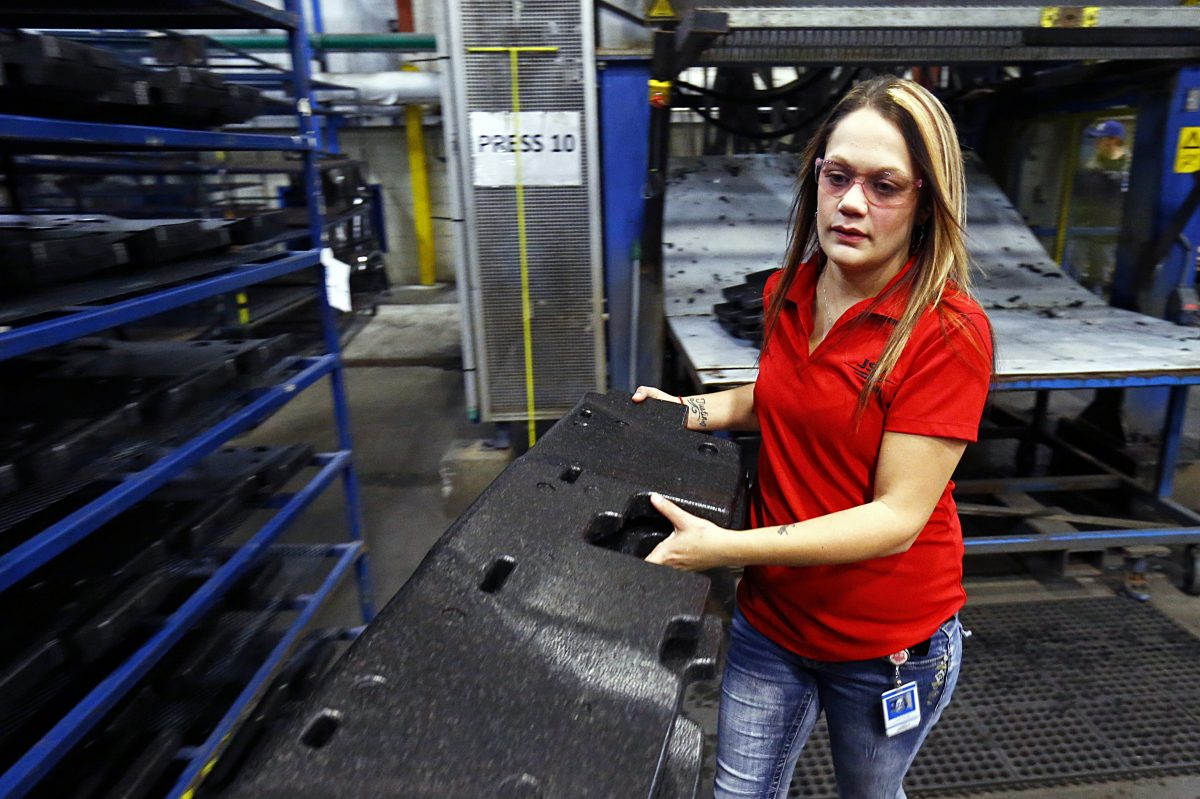 Mold tech Haley George takes parts to a rack to cool after they have been molded at the JSP International in Tullahoma, Tennessee. JSP's U.S. corporate headquarters are in Wayne. Just over a year ago,  George was in jail, recovering from a drug addiction. Now, she says, her life has completely changed for the better. (Wade Payne/AP)