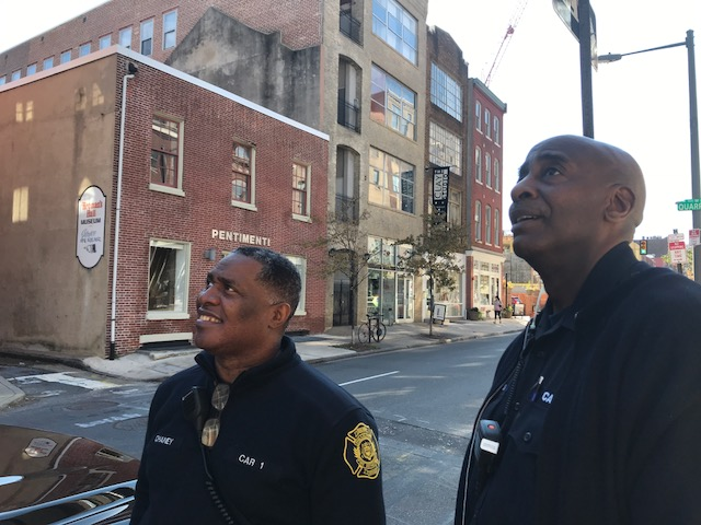 Firefighters Ed Chaney and J.T. Williams look up at the sky billboard near 2nd and Race Streets in Old City.