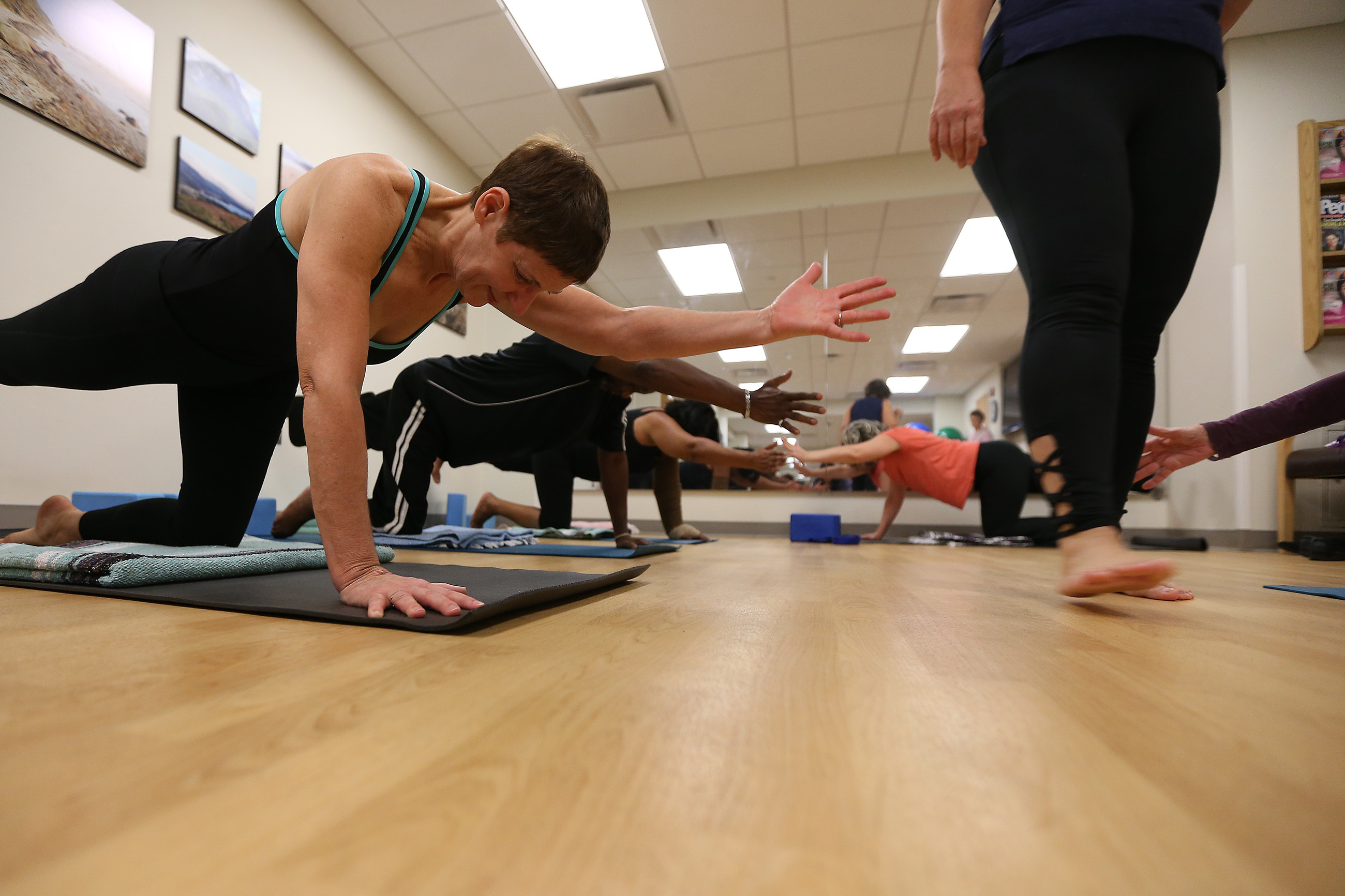 Jennifer Hook, 60, of West Philadelphia, moves into a pose during a yoga class at the Hospital of the University of Pennsylvania.