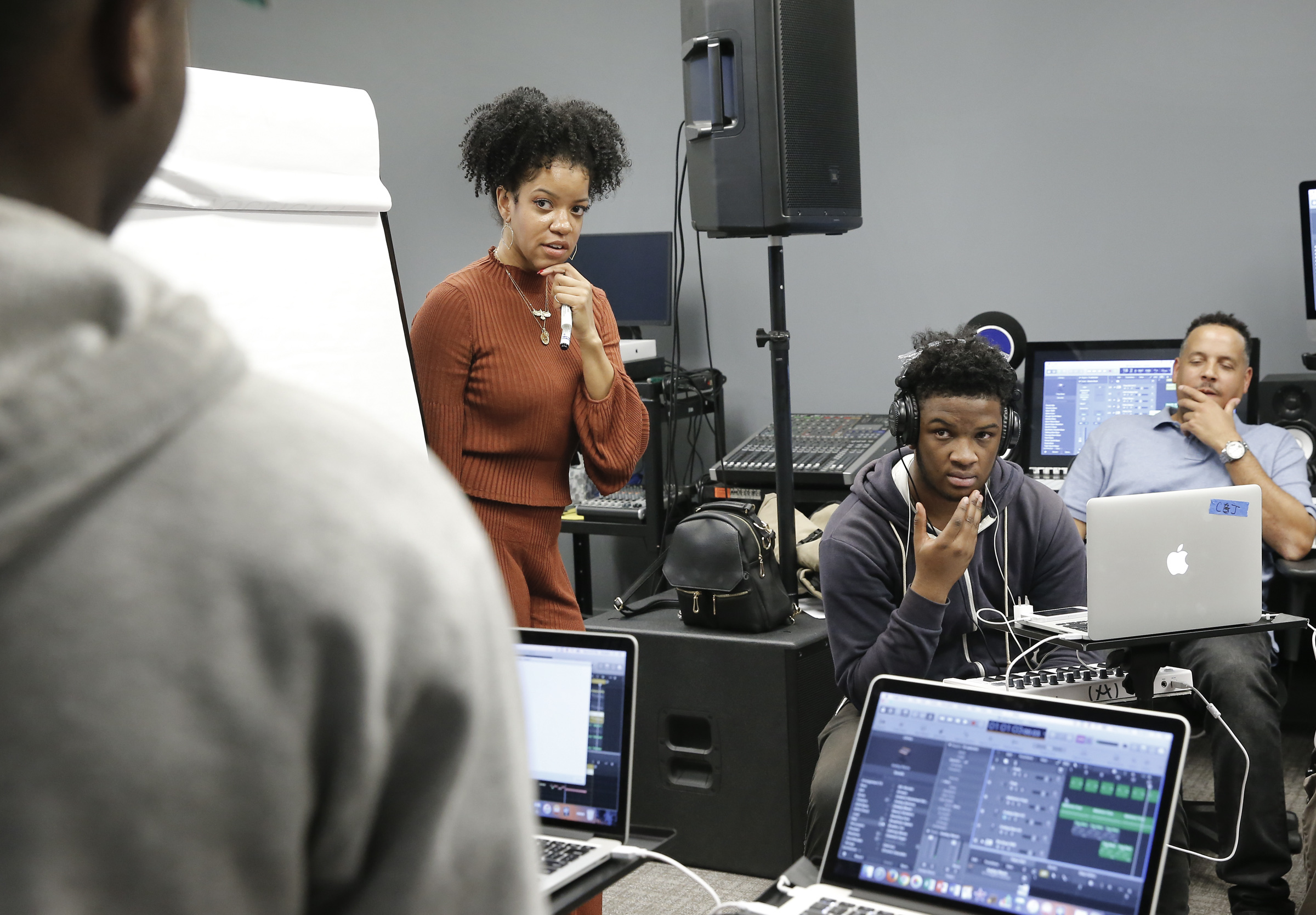 "Songwriting music instructor Kristal Oliver listens to the High School for the Creative and Performing Arts senior Jelani Green (far left) during the ""Songwriting 101"" class at the Philadelphia School District headquarters."
