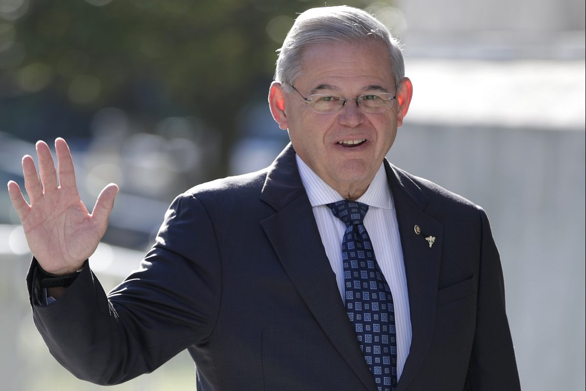Sen. Bob Menendez waves to reporters while arriving at the Martin Luther King, Jr. Federal Courthouse.