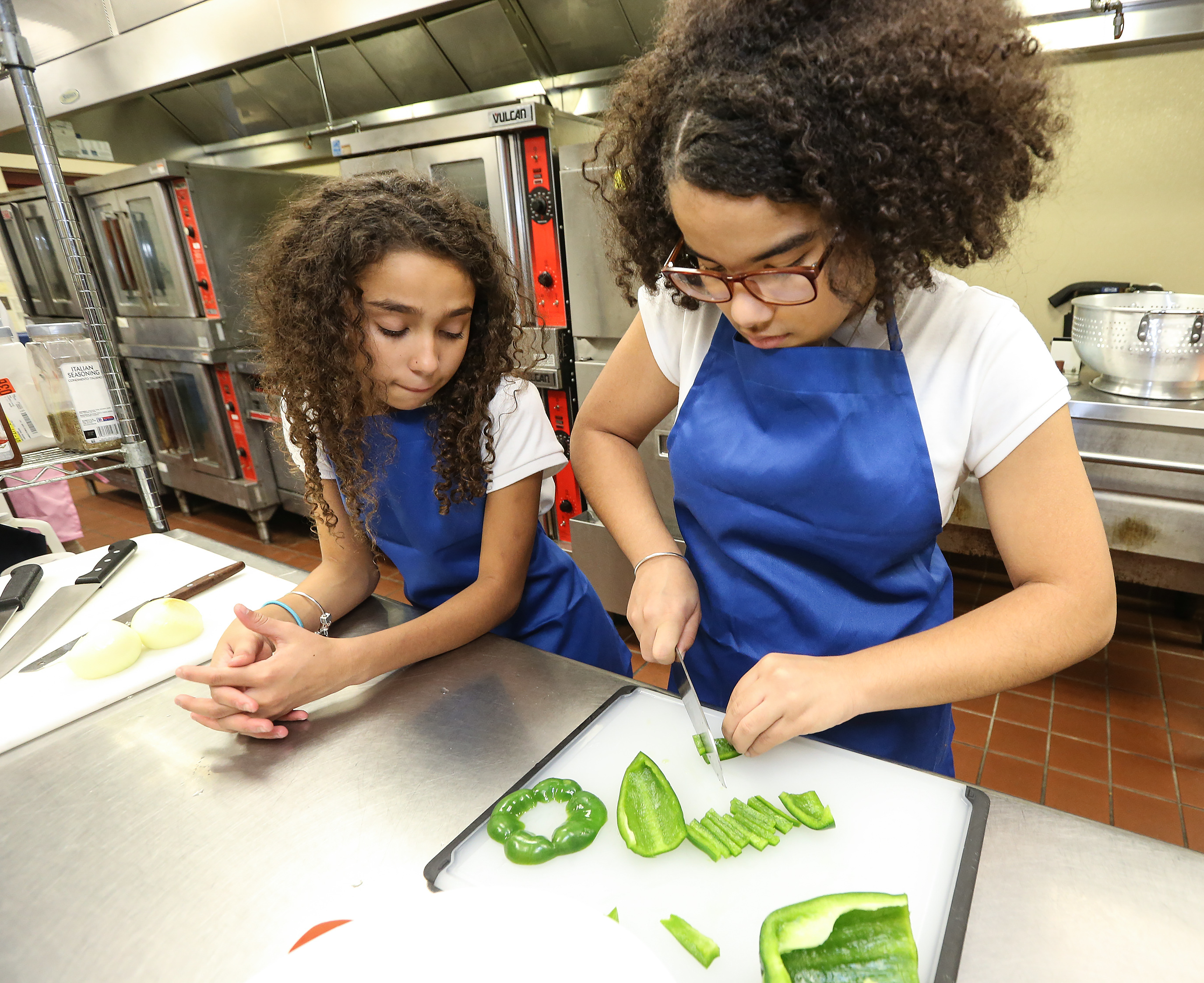 Jailee Torres, 6th grade, watches Chrismeilin Acosta, 8th grade cut peppers while prepping the ingredients for beef stir fry.