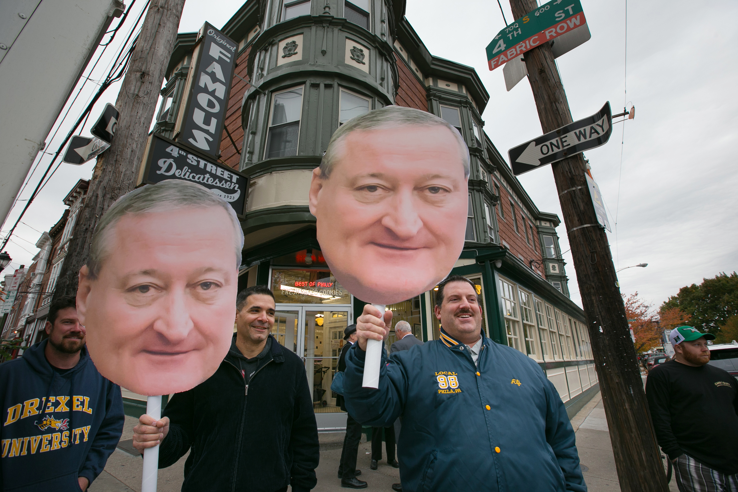 Electricians from local 98, Joseph Fareri, left, and Alfio Sorbello, right, hold up photos of Mayor James Kenney, in front of Famous 4th Street Deli, in Philadelphia, Tuesday, Nov. 7, 2017.