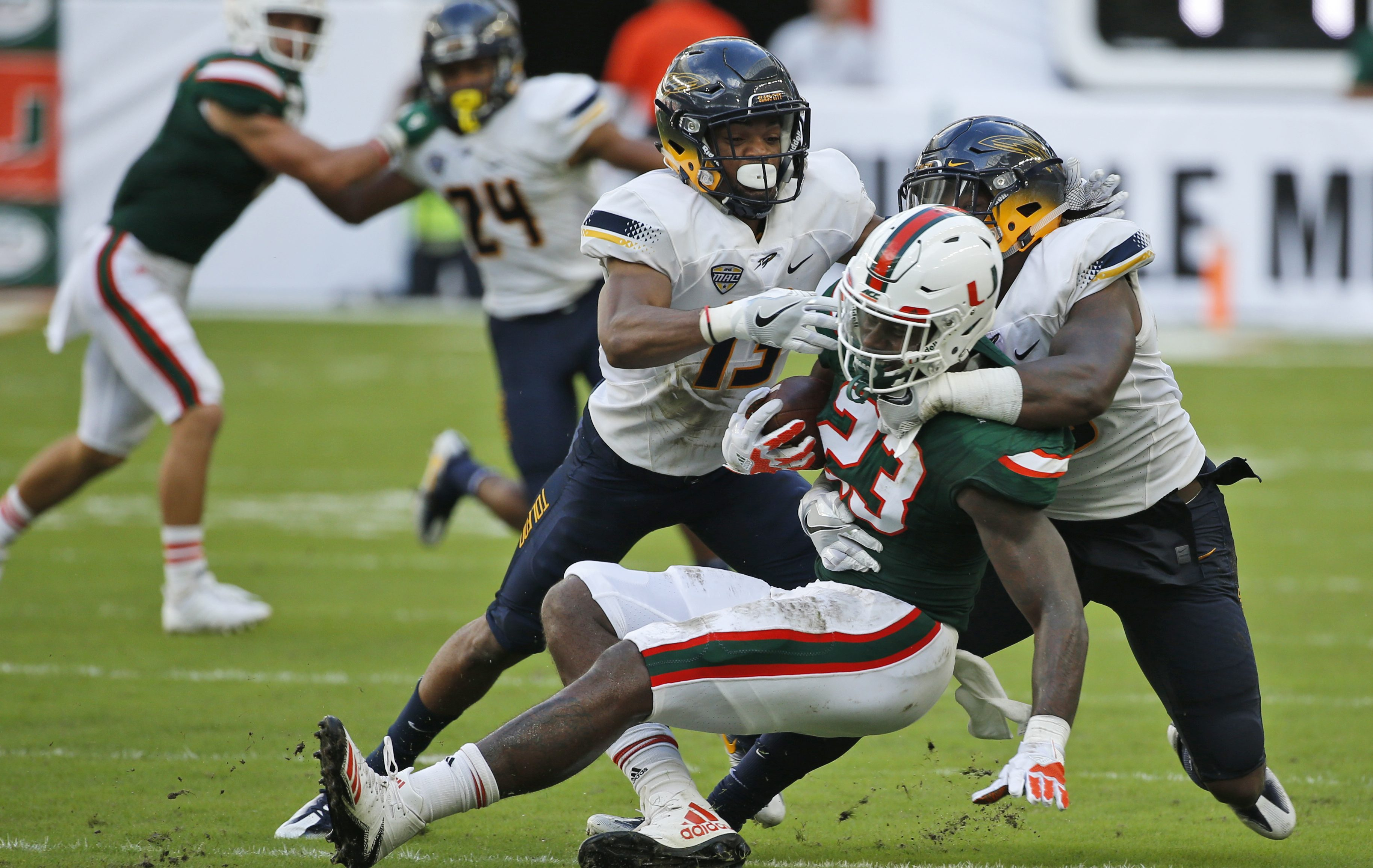 Toledo defensive back Ka´dar Hollman, left, and linebacker Ja´Wuan Woodley, right, take down Miami tight end Christopher Herndon IV (23) during the first half of an NCAA College football game, Saturday, Sept. 23, 2017 in Miami Gardens, Fla. (AP Photo/Wilfredo Lee)