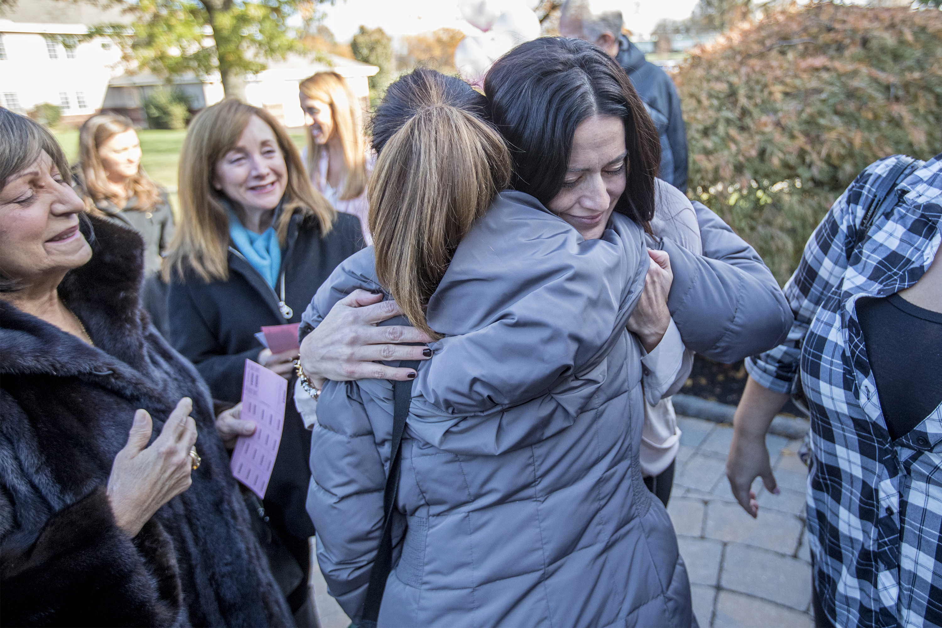 Kristen Masciantonio, right, whose daughter Gianna, 3, has miraculously survived a life-threatening blood disorder since birth, gets a hug from one of the 300 women at Sunday´s For the Love of Grace Foundation fundraiser at St. Cyril of Jerusalem Church in Jamison, Bucks County, for pediatric brain tumor research..