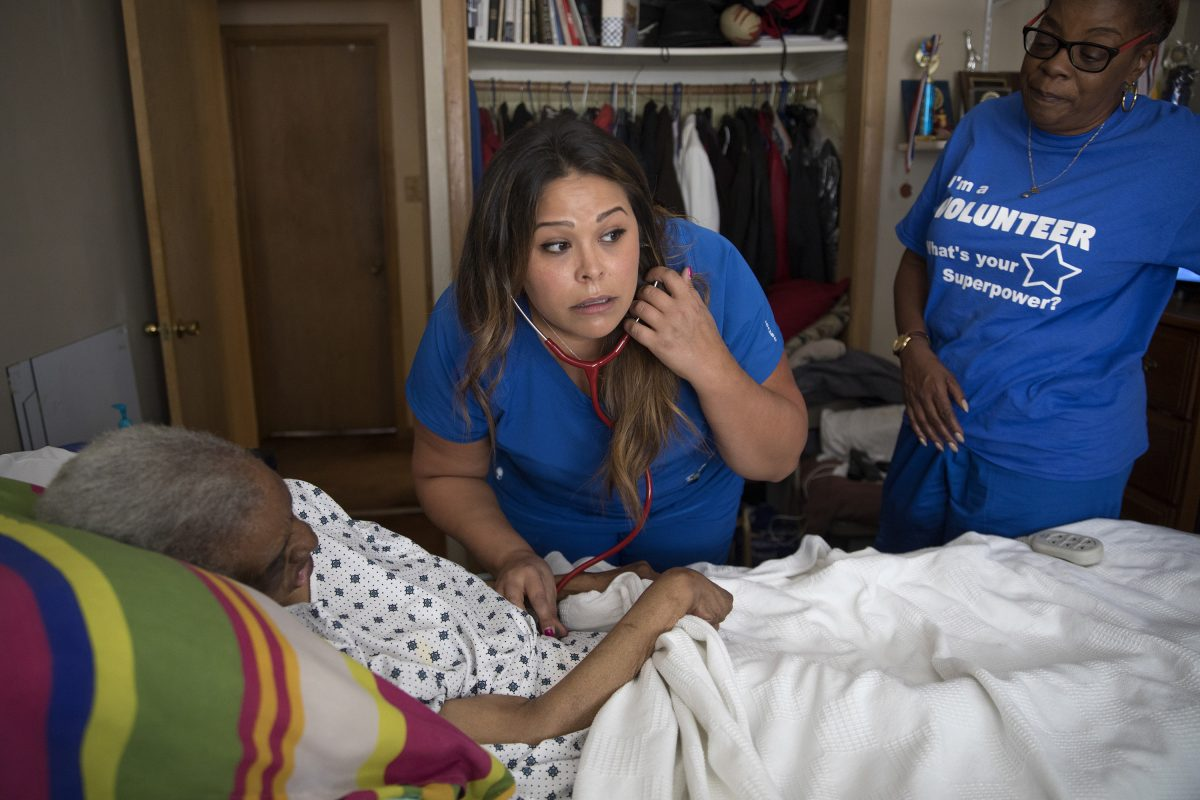 RN Jennifer Ruiz of Unity Hospice (center) checks the vital signs of Juanita Davis as her daughter Dorothy Parrott, who is the volunteer coordinator for Unity Hospice, stands by at her home in Calumet City, Ill.