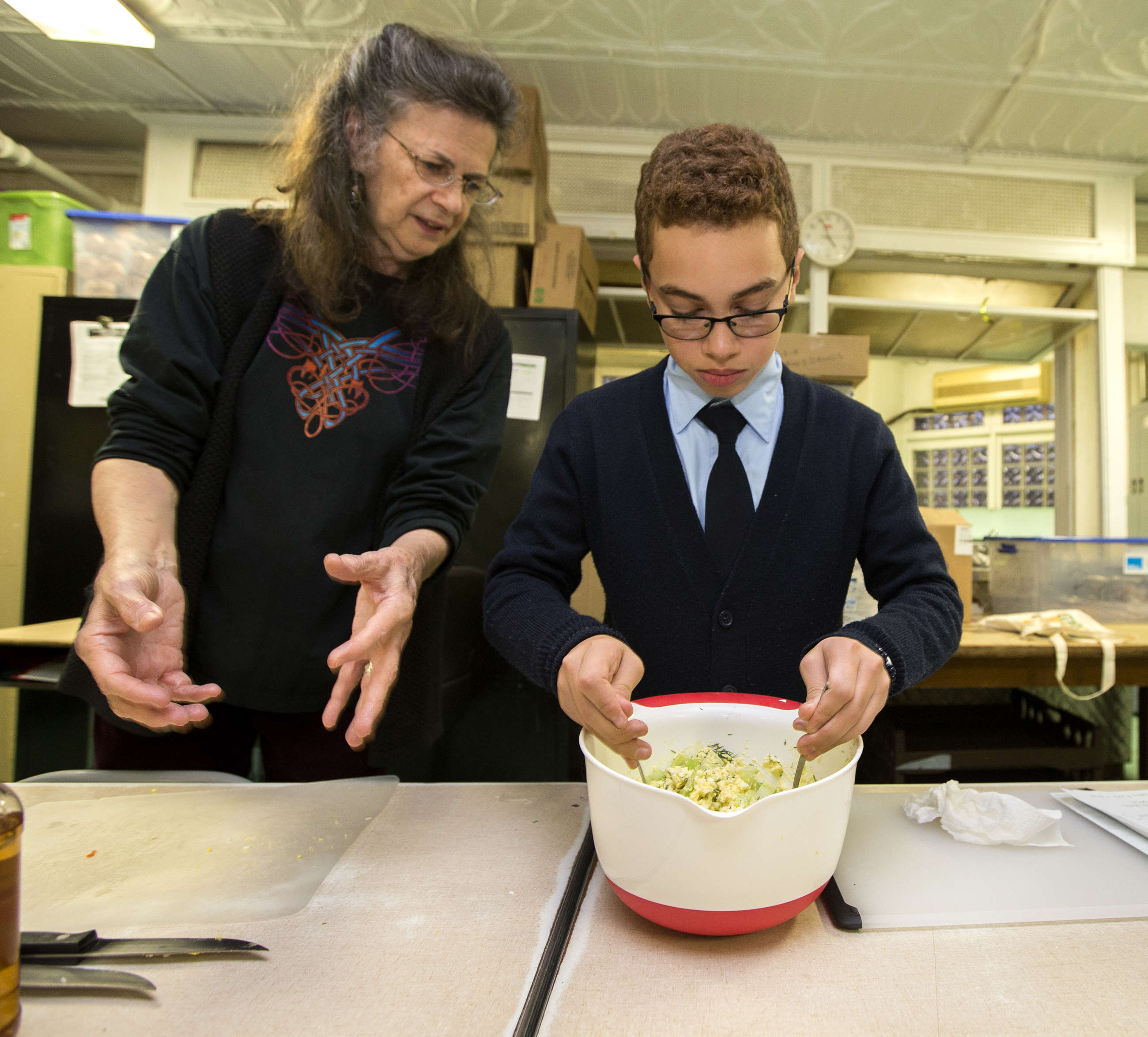 Volunteer Maria Brown, left, instructs Antonio Santiago, right, as he mixes up the egg salad.