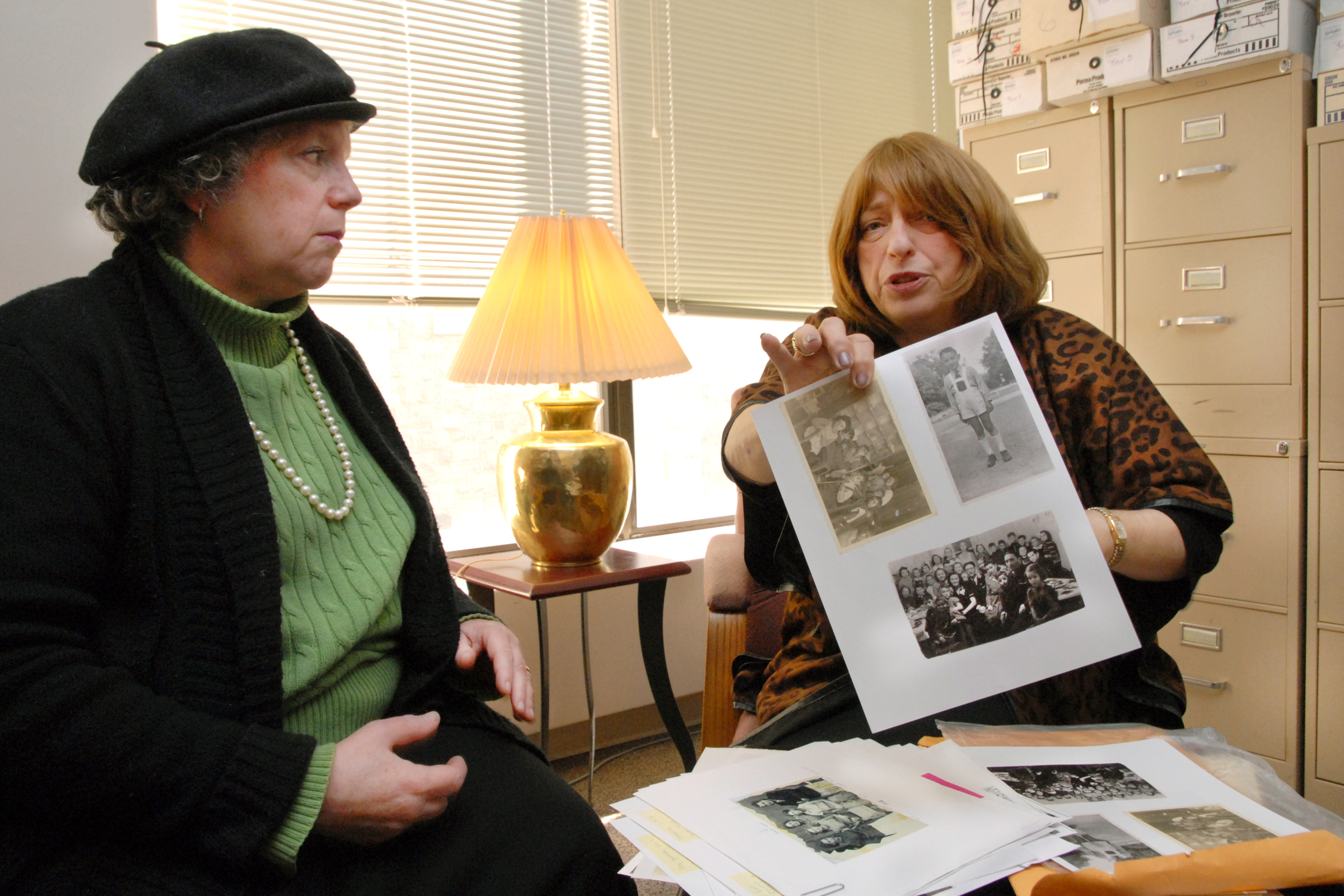 Bea Hollander-Goldfein holds photos of her half brother Jack Hollander, who is a Holocaust survivor, while Nancy Isserman looks on. The two are co-directors of the Transcending Trauma Project.