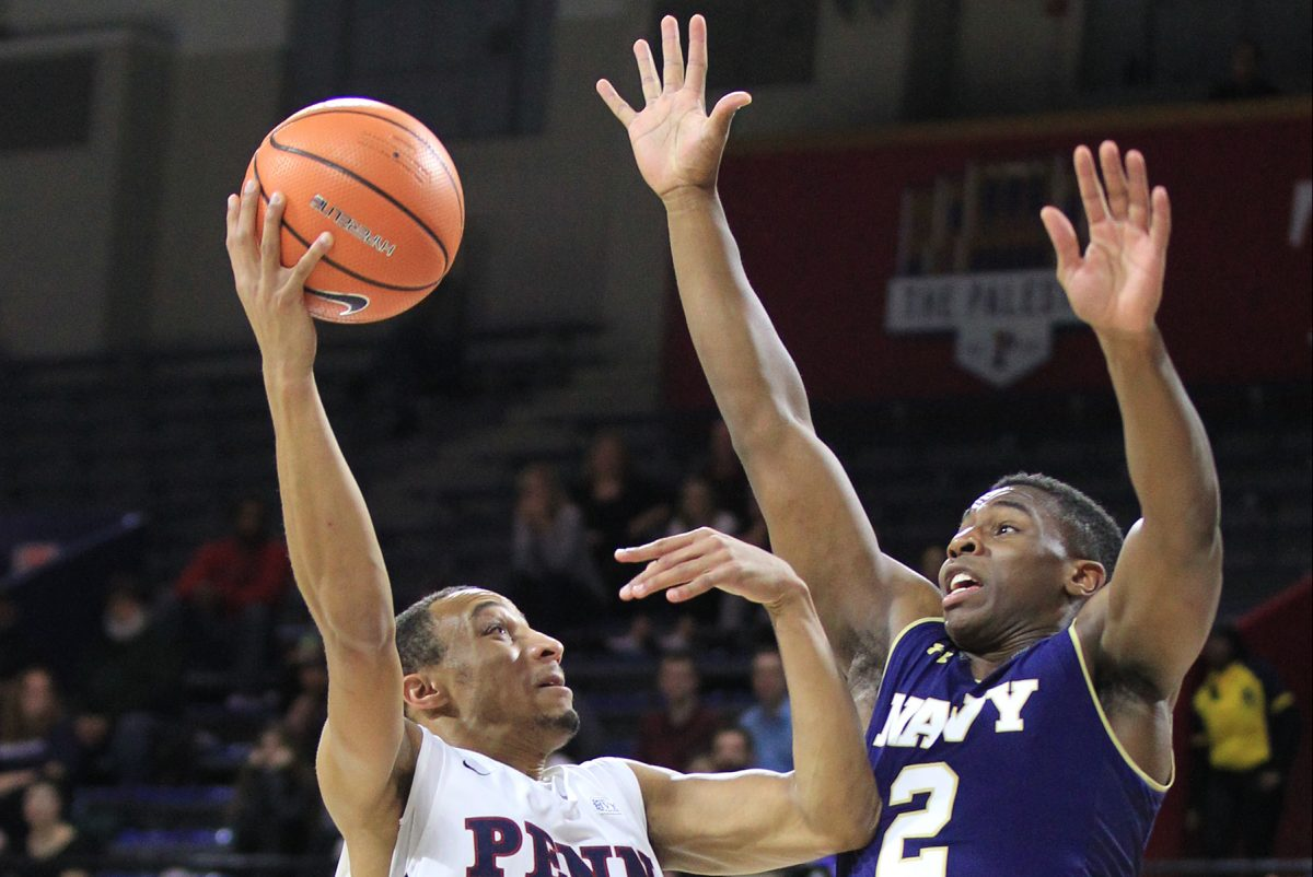 Darnell Foreman, left, of Penn goes up for a shot against Hasan Abdullah of Navy during 1st half at the Palestra at the University of Pennsylvania on Nov. 15, 2017. CHARLES FOX / Staff Photographer