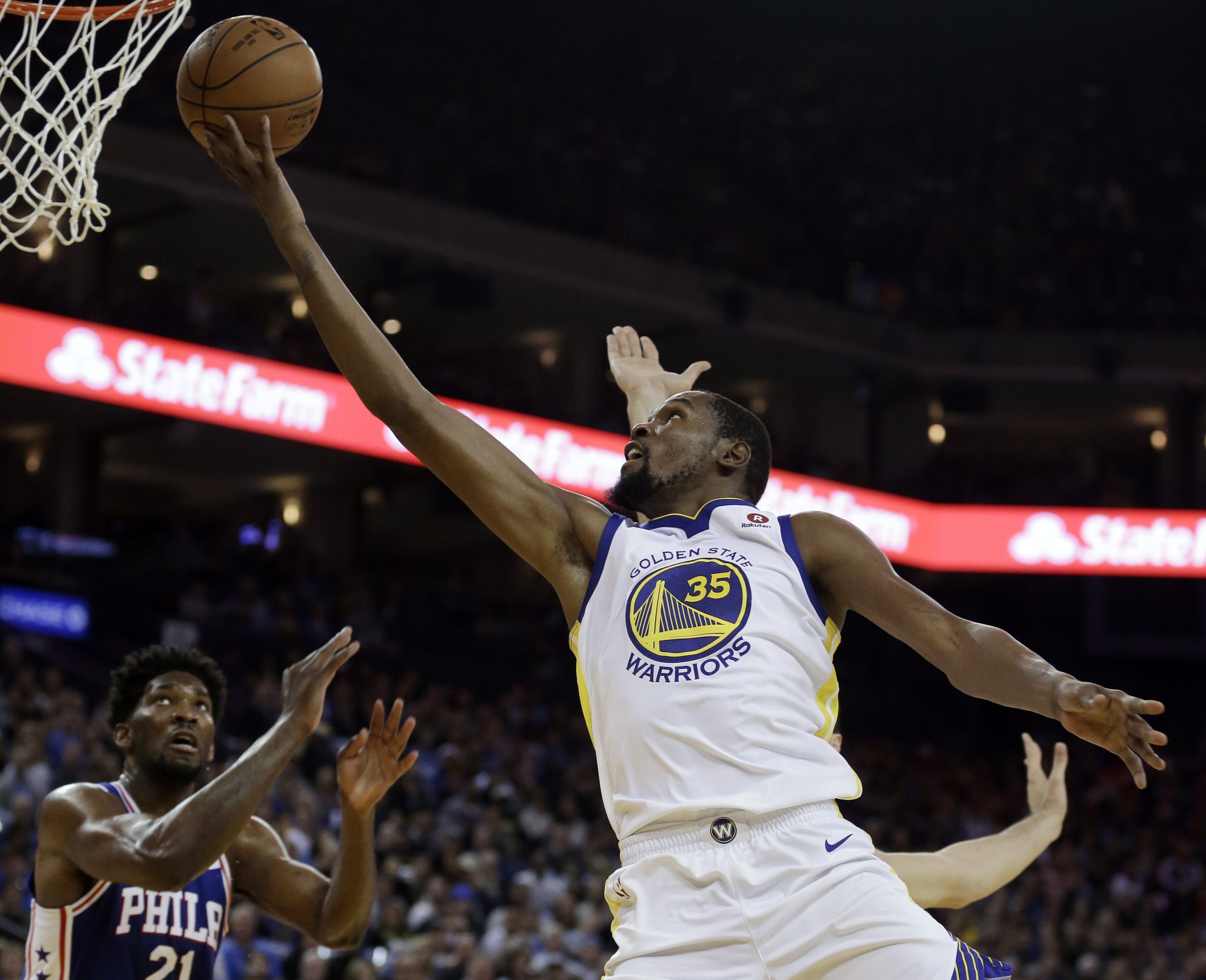 Golden State Warriors´ Kevin Durant (35) lays up a shot over Philadelphia 76ers´ Joel Embiid (21) during the first half of an NBA basketball game Saturday, Nov. 11, 2017, in Oakland, Calif. (AP Photo/Ben Margot)