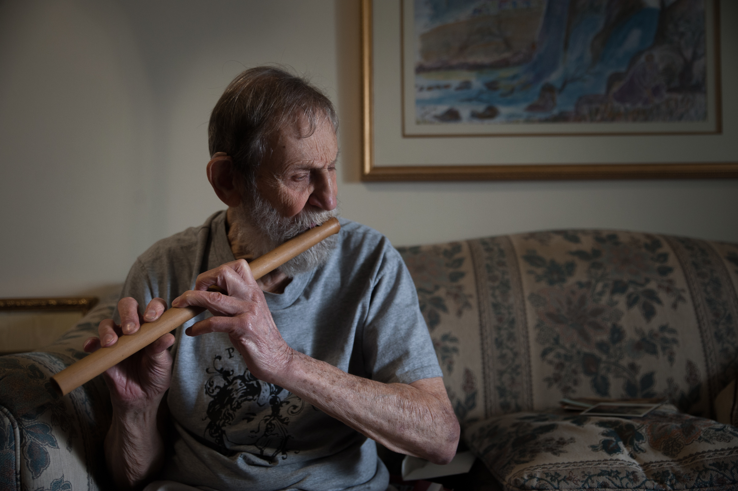 """Robert Mellin, known as """"Uncle Rocky"""" to friends and family, plays a flute acquired on one of his voyages in his apartment at 13th and Lombard streets, June 5th, 2017. Mellin has a reputation of being an intrepid traveller, and is about to embark on a three month journey to Cambodia, Laos, Vietnam, and Thailand. CAMERON B. POLLACK / Staff Photographer"""
