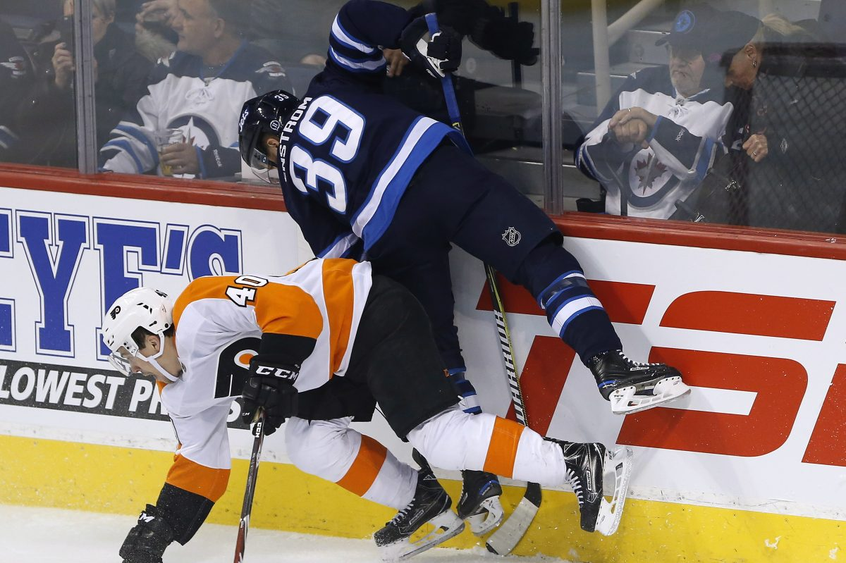 The Flyers Jordan Weal (40) and Winnipeg's  Toby Enstrom  collide behind the Jets net during first-period action.