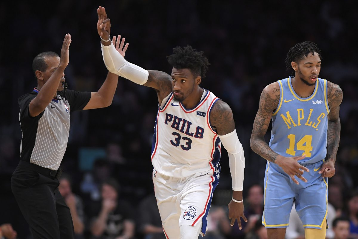 Sixers forward Robert Covington (center) gestures after hitting a 3-point shot as Los Angeles Lakers forward Brandon Ingram stands behind on Wednesday.