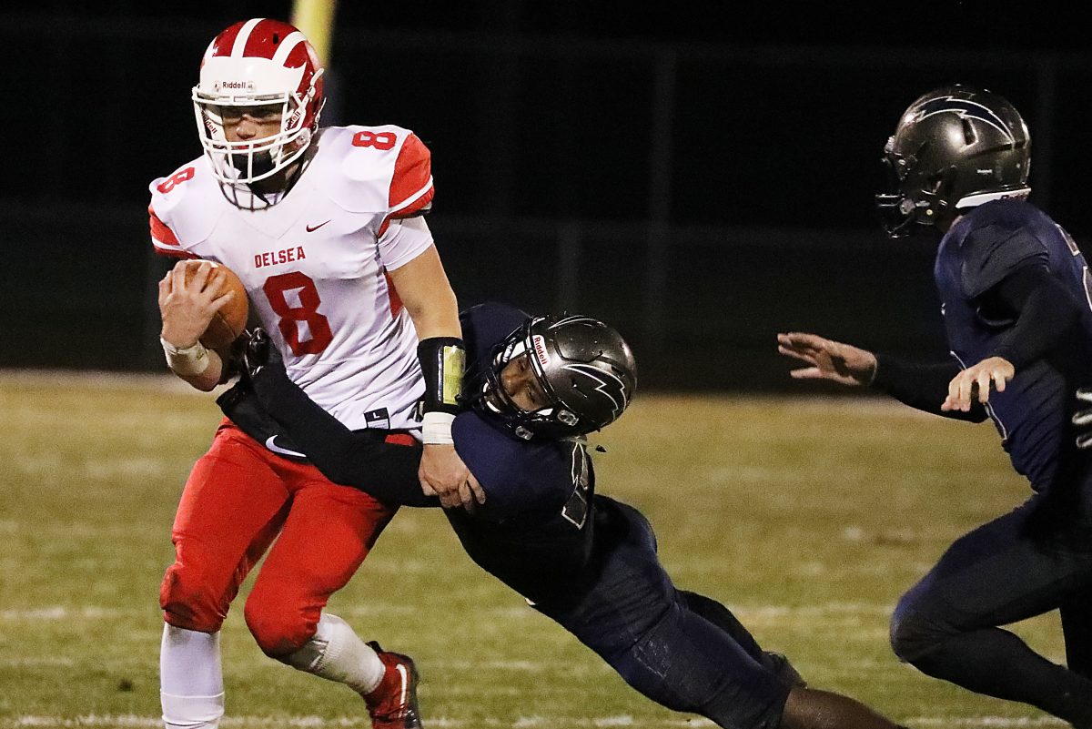 Delsea quarterback Mason Maxwell (left) fights a tackle by Timber Creek's Sage Brown on Friday.