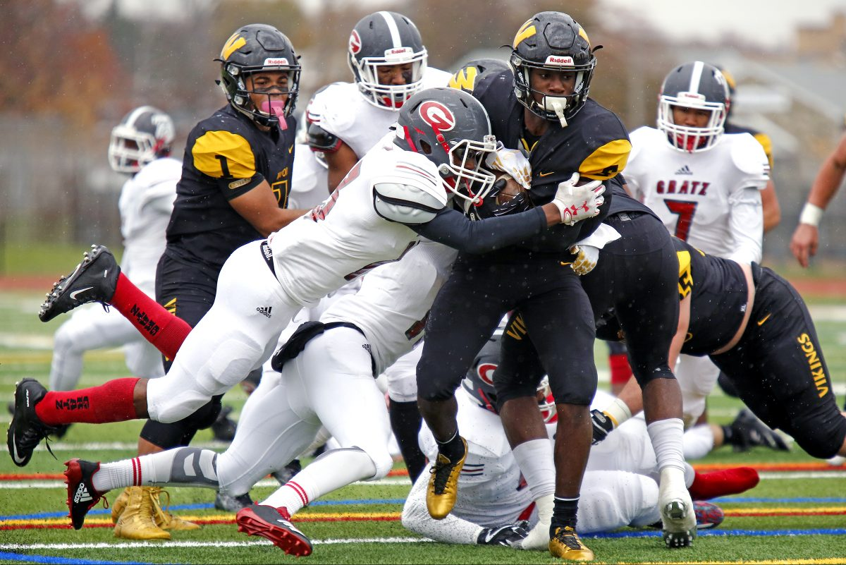 Archbishop Wood's Nasir Peoples carries Simon Gratz defenders Jawon Harrison (middle, airborne) and Terrell Stewart (hidden) for yardage in Saturday afternoon's PIAA District 12 Class 5A football final.