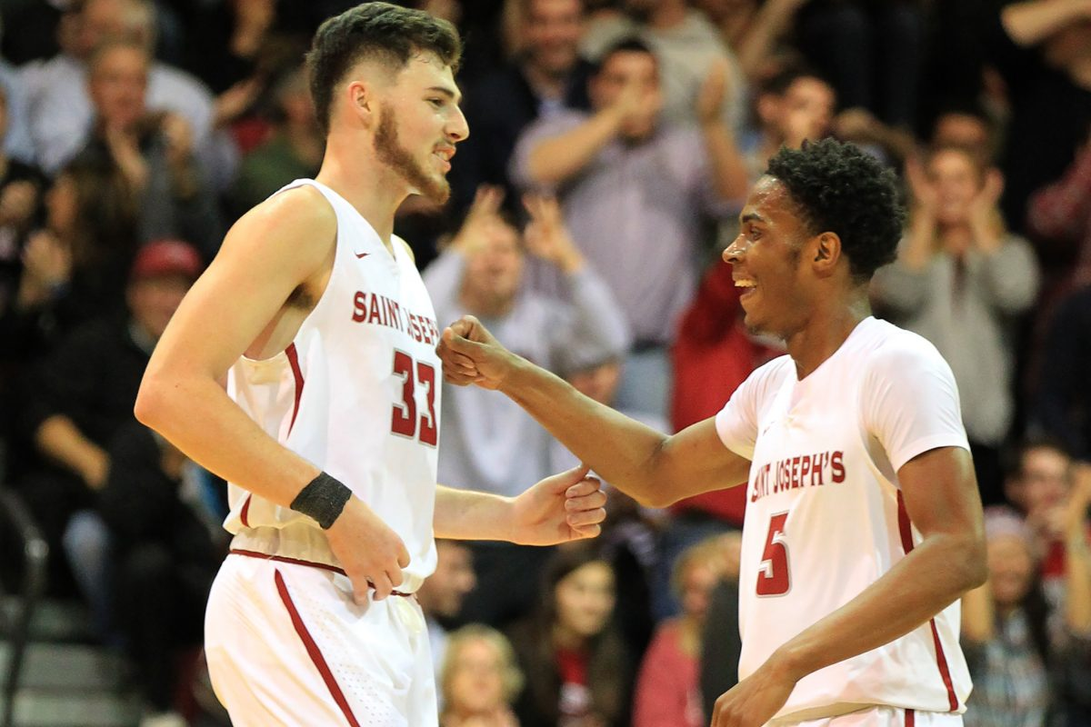 Taylor Funk, left, of St. Joseph's celebrates with teammate Nick Robinson after Funk's 3-pointer forced Princeton to call a timeout in the 2nd half on Nov. 18, 2017. Funk led all scorers with 23 points in St. Joe's 71-58 victory. CHARLES FOX / Staff Photographer