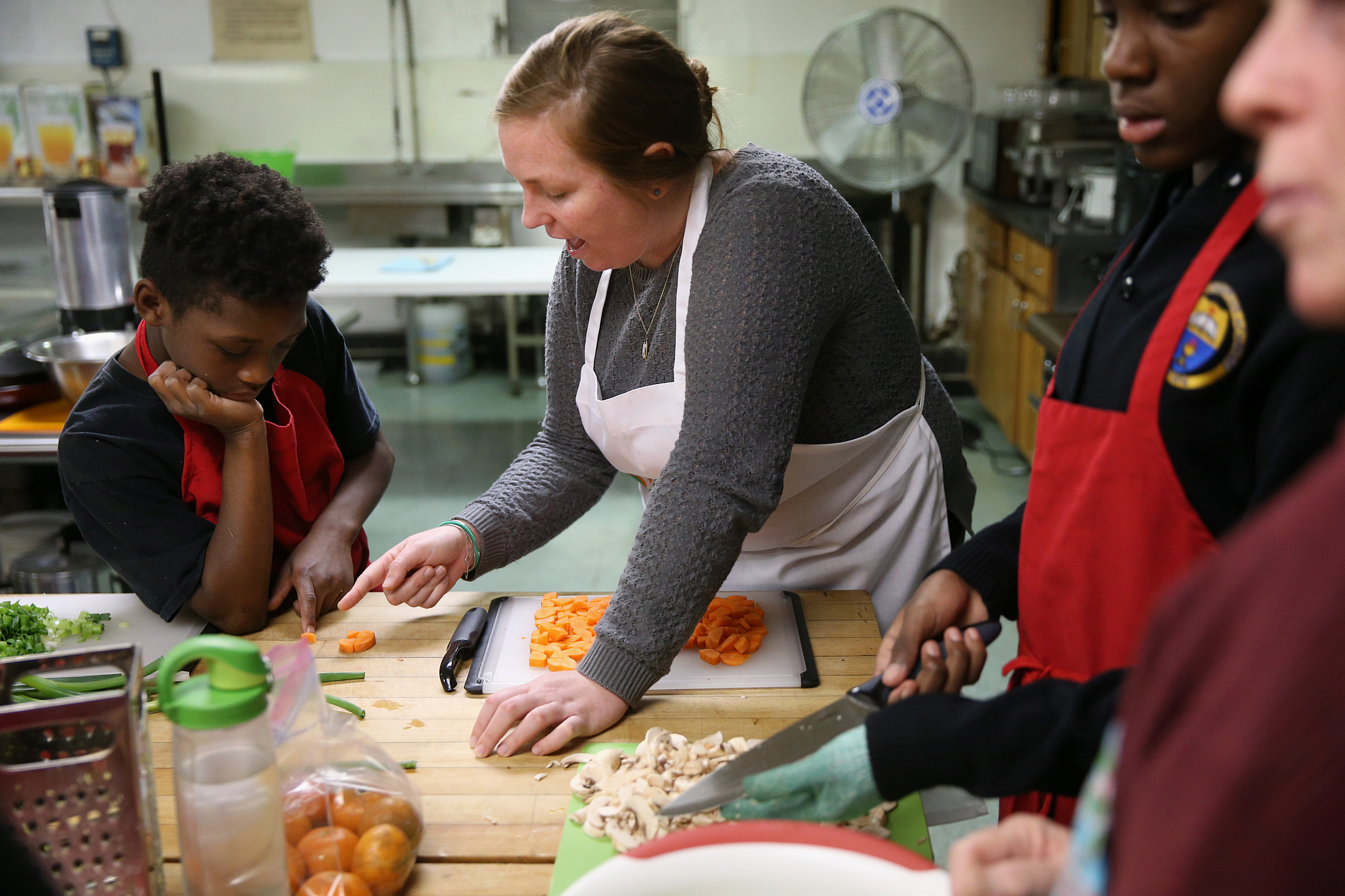 Instructor Maddy Booth, center, gives Germaine Glover, 10, a quick lesson in fractions using a carrot slice.