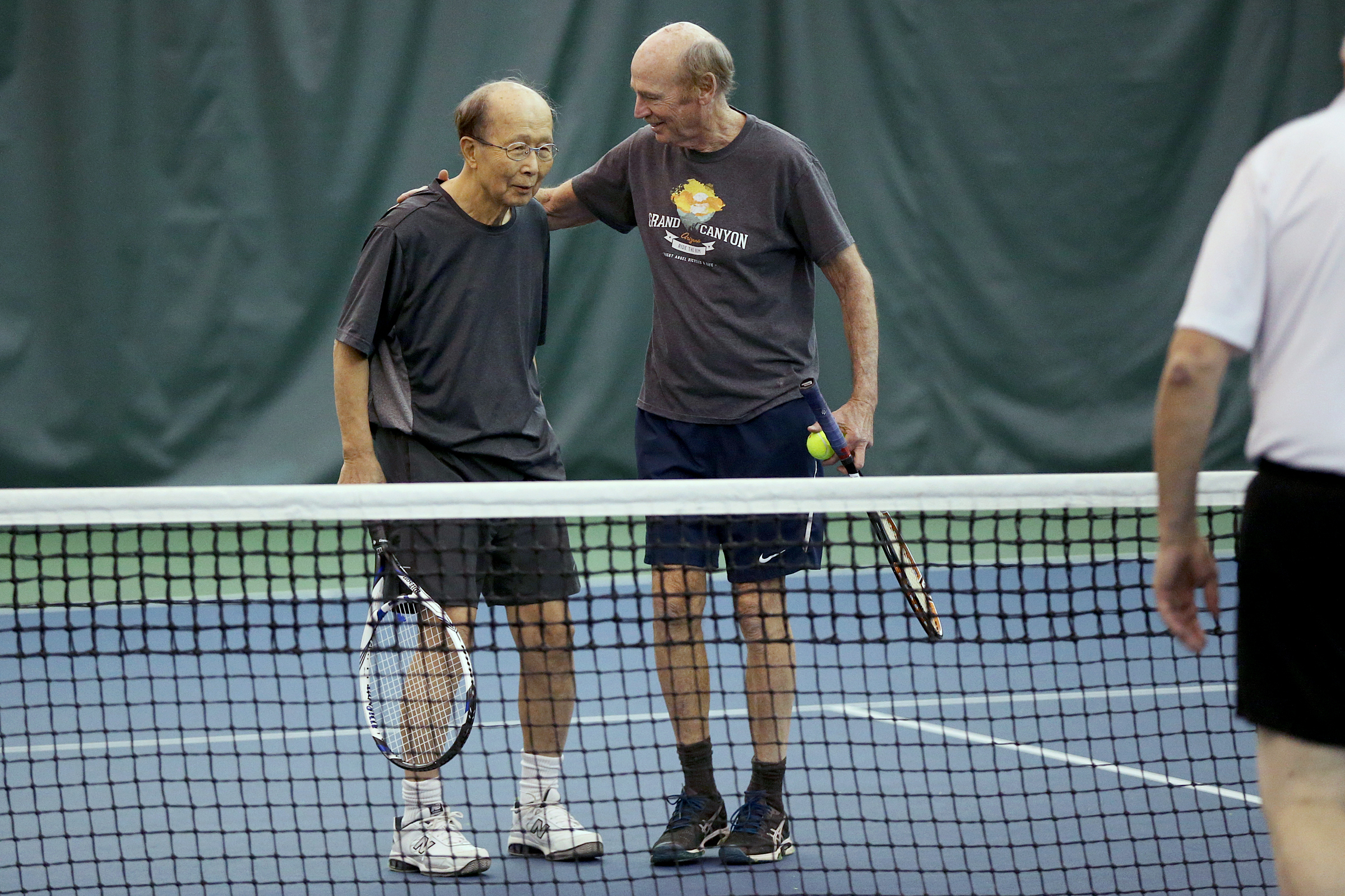 David Fultz, 75, (right) congratulates tennis partner Chong-sik Lee, 86, professor emeritus of political science at the University of Pennsylvania, after the pair won a match during their weekly tennis session at the Great Valley Racquet Club in Malvern. Lee, who escaped from North Korea during the Korean War, is publishing a memoir.