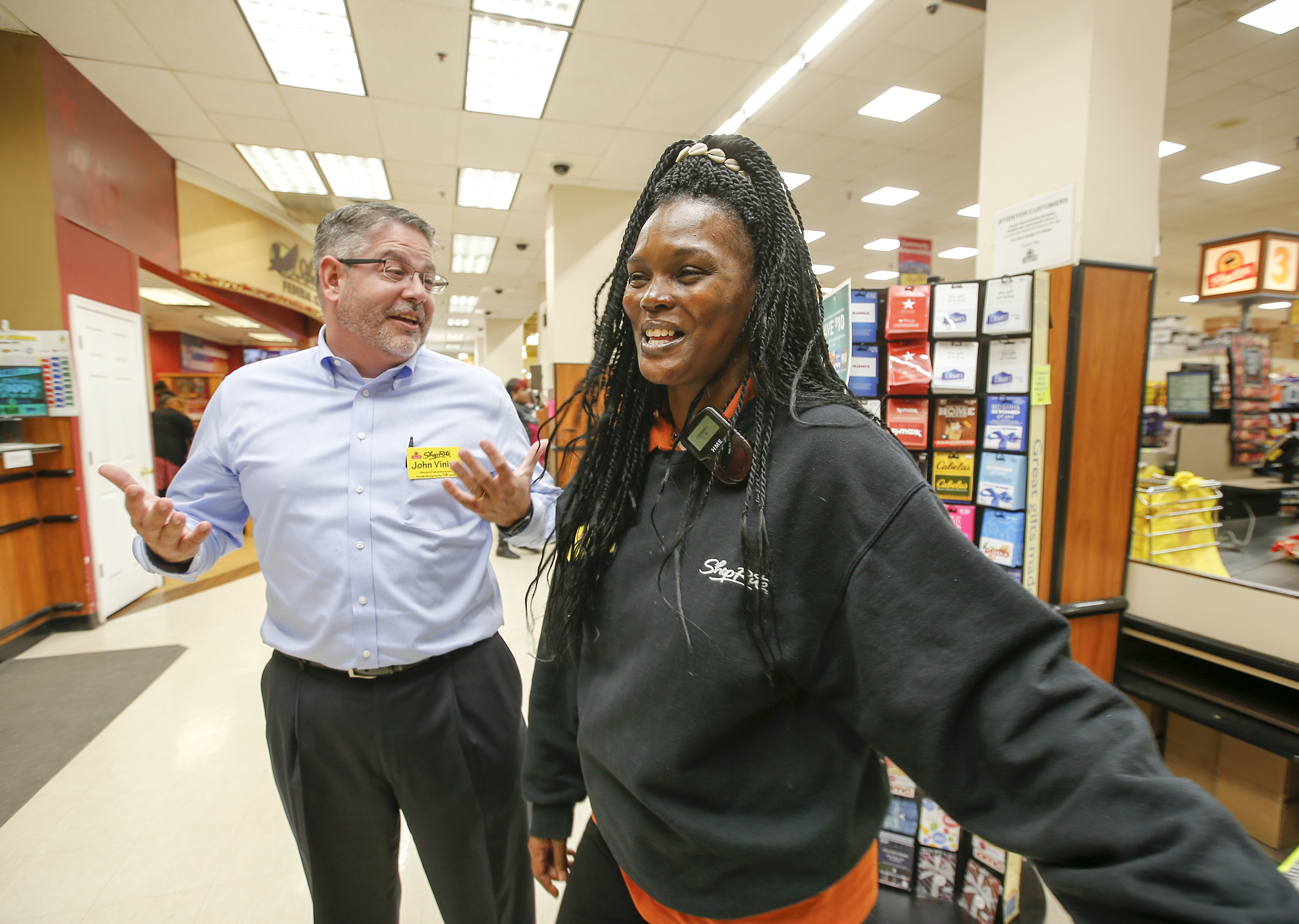 ShopRite employee LaShawna Bennett (right) shares a laugh last week with John Vining, director of human resources for Browns Super Stores Inc. at the Roxborough ShopRite. YONG KIM / Staff Photographer