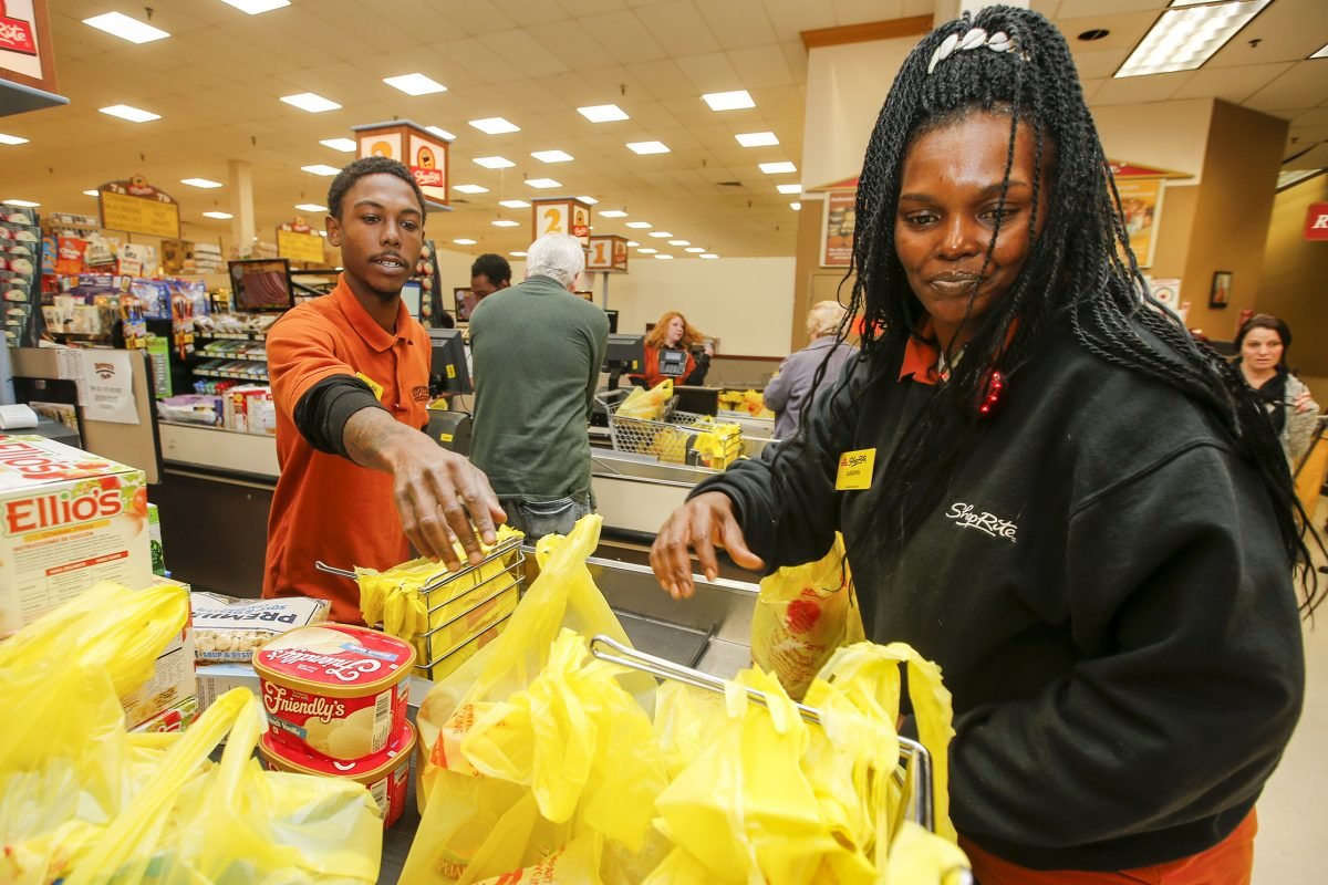 ShopRite employee LaShawna Bennett (right) helps bag items with Shakiel Taylor at ShopRite's Roxborough store last week. Bennett and Taylor were both enrolled in a program that guaranteed jobs to ex-offenders who completed cashier training.