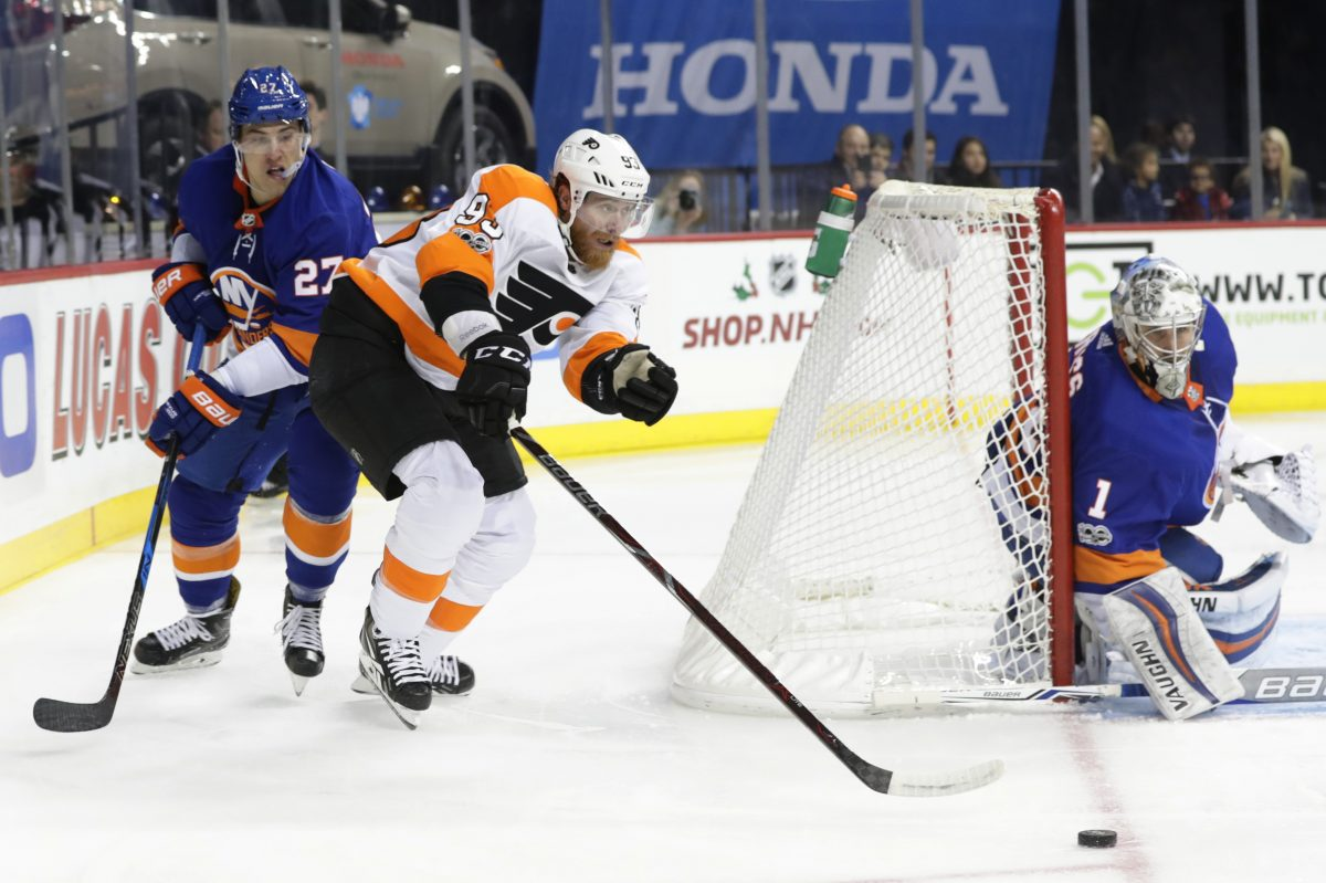 Flyers right wing Jakub Voracek (center) passes away from New York Islanders Anders Lee (left) and goalie Thomas Greiss during the first period of the Flyers 4-3 overtime loss to the Islanders.