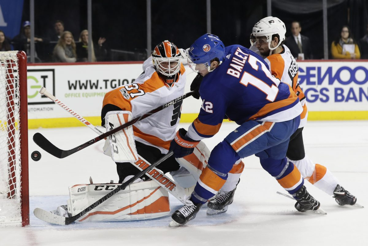 Islanders' Josh Bailey (12) shoots the puck past Flyers goalie Brian Elliott (left) for the game-winning goal during the overtime period of the Flyers' 4-3 loss.