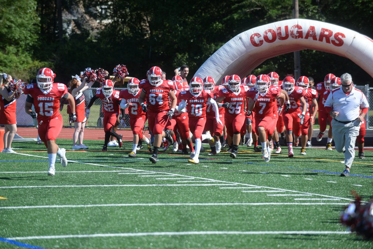 Dante Gazzola (15) leads Cherry Hill East football team on the field for the season opener vs. Paul VI.