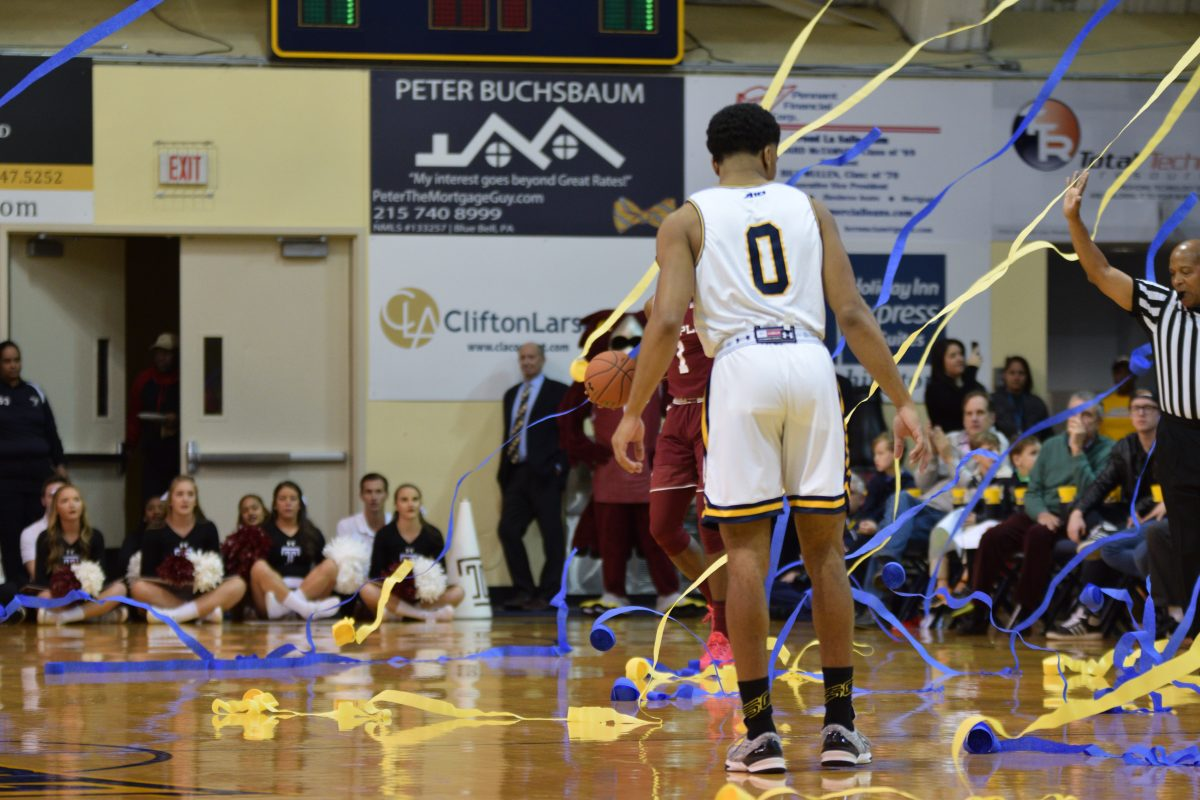 Redshirt junior guard Pookie Powell walks among the streamers thrown by La Salle fans onto the court in the first half of Sunday's game against Temple at the Gola Arena.
