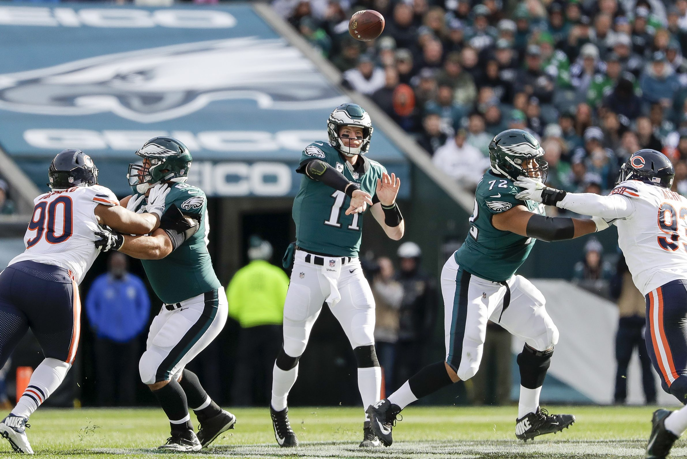 Eagles quarterback Carson Wentz throws a first-quarter pass as offensive linemen Stefen Wisniewski and Halapoulivaati Vaitai block Chicago Bears defensive end Jonathan Bullard (left) and outside linebacker Sam Acho (right) on Sunday.