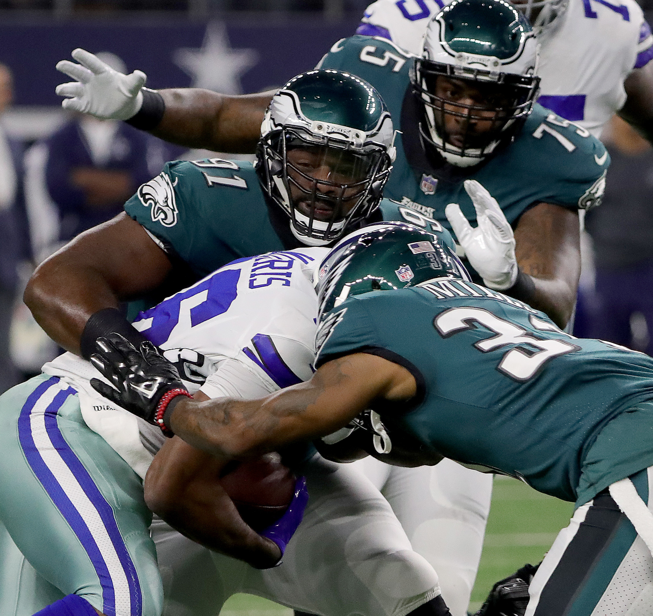 Eagles' Fletcher Cox, left, Jalen Mills, center, and Vinny Curry, right, stop Cowboys' running back Alfred Morris.