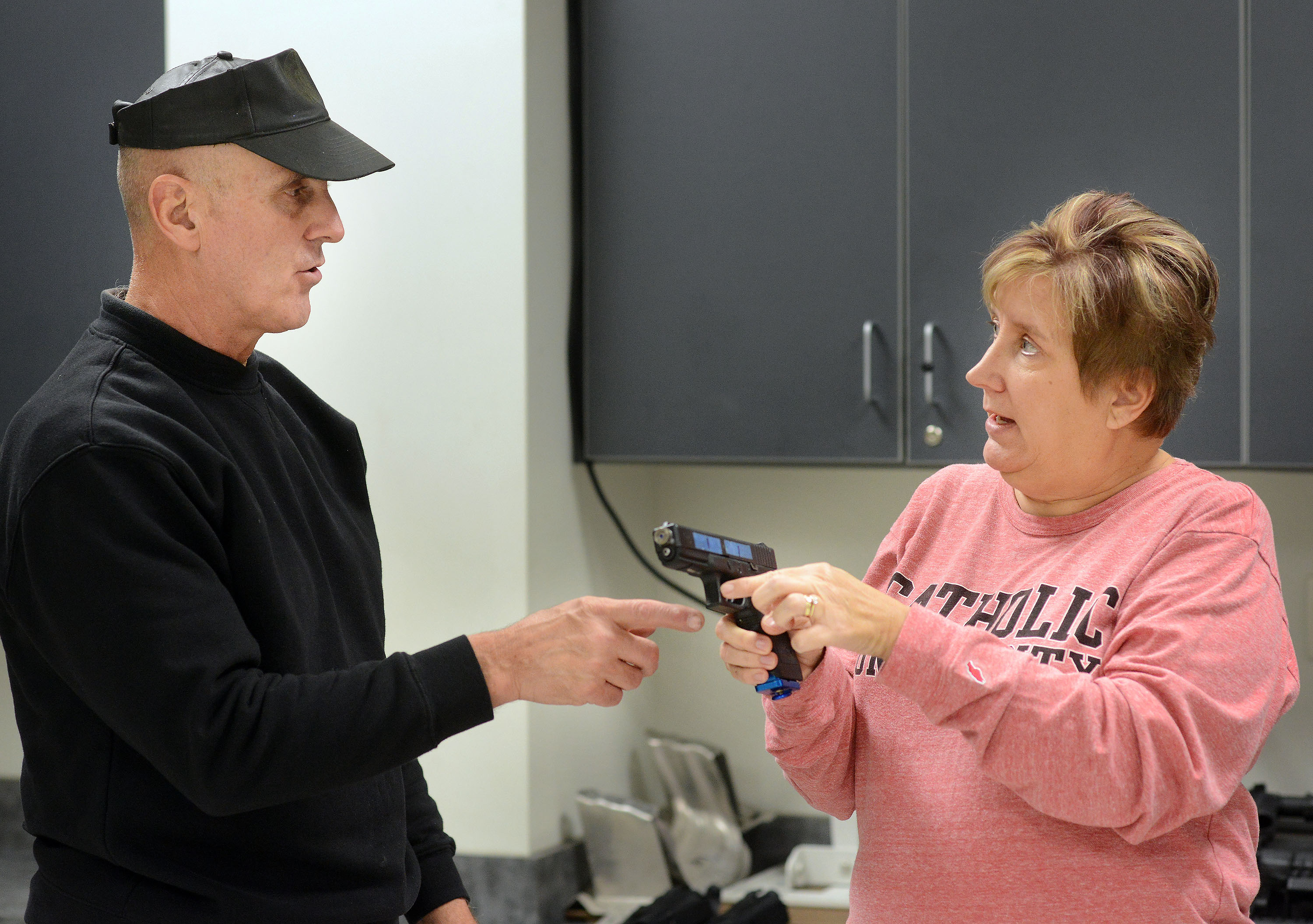 Officer Steve Dintino of East Pikeland Police (left) shows Nancy Griffith of Spring City how to shoot a Glock pistol modified for simulated training scenarios during the Citizens´ Police Academy at the Chester County Intermediate Unit in Downingtown.