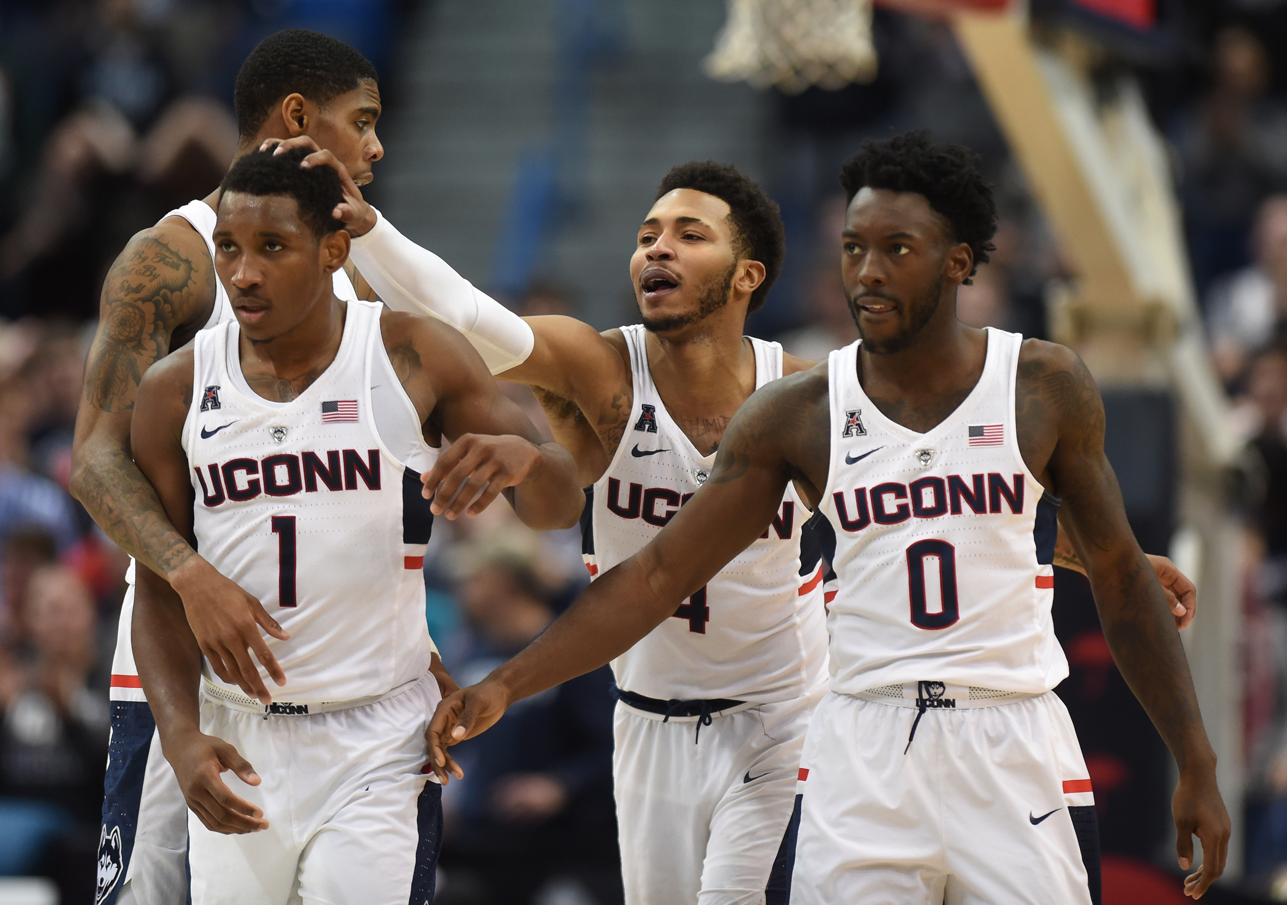 From left, Connecticut Huskies guards Christian Vital (1), Jalen Adams (4) and Antwoine Anderson (0) react near the conclusion of a victory over Monmouth at the XL Center Saturday, Dec. 2, 2017 in Hartford, Conn. The Huskies beat the Hawks 84-81 in overtime. (Brad Horrigan/Harford Courant/TNS)