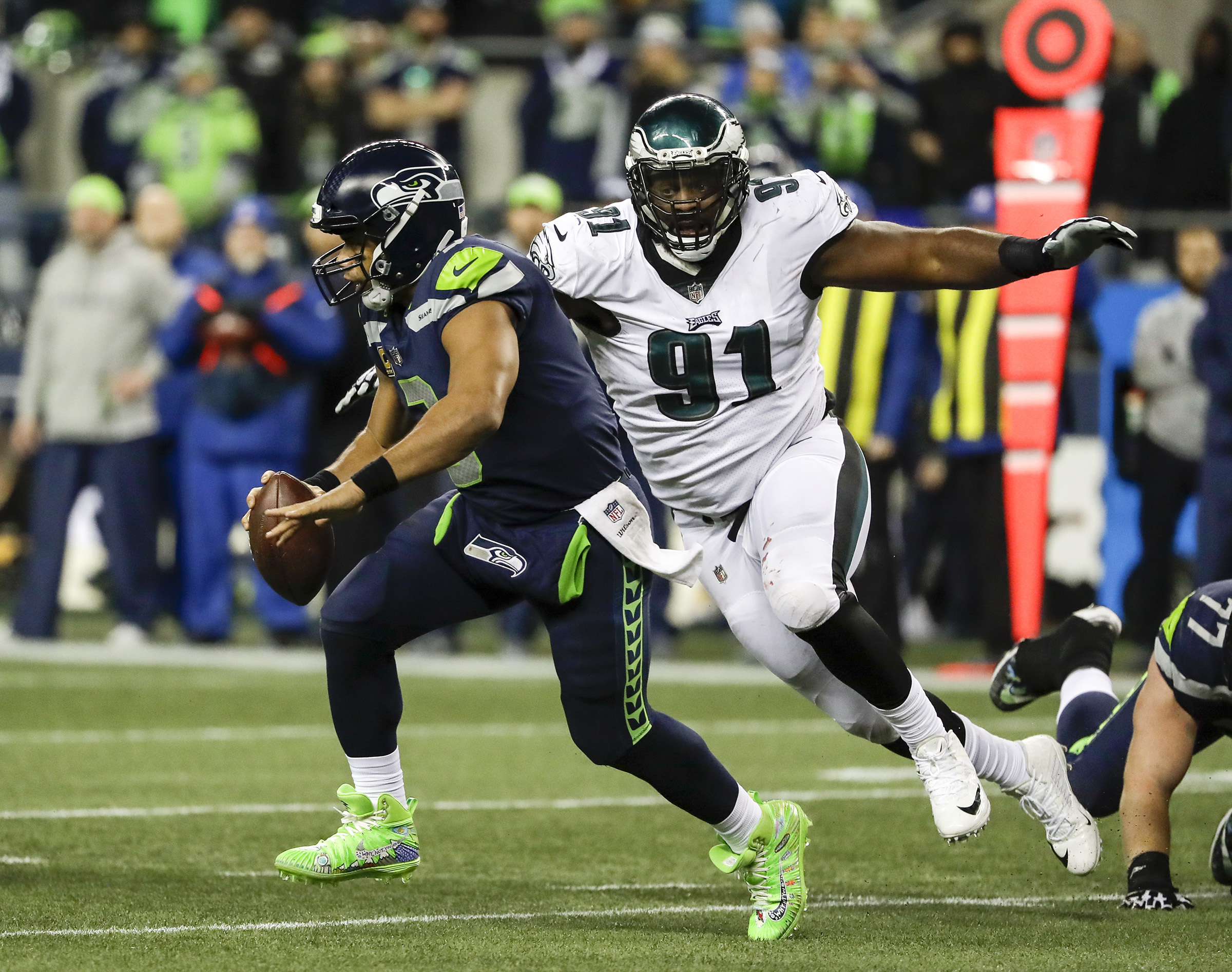 Seattle Seahawks quarterback Russell Wilson runs past Eagles defensive tackle Fletcher Cox in the fourth-quarter on Sunday, December 3, 2017 at CenturyLink Field in Seattle. YONG KIM / Staff Photographer