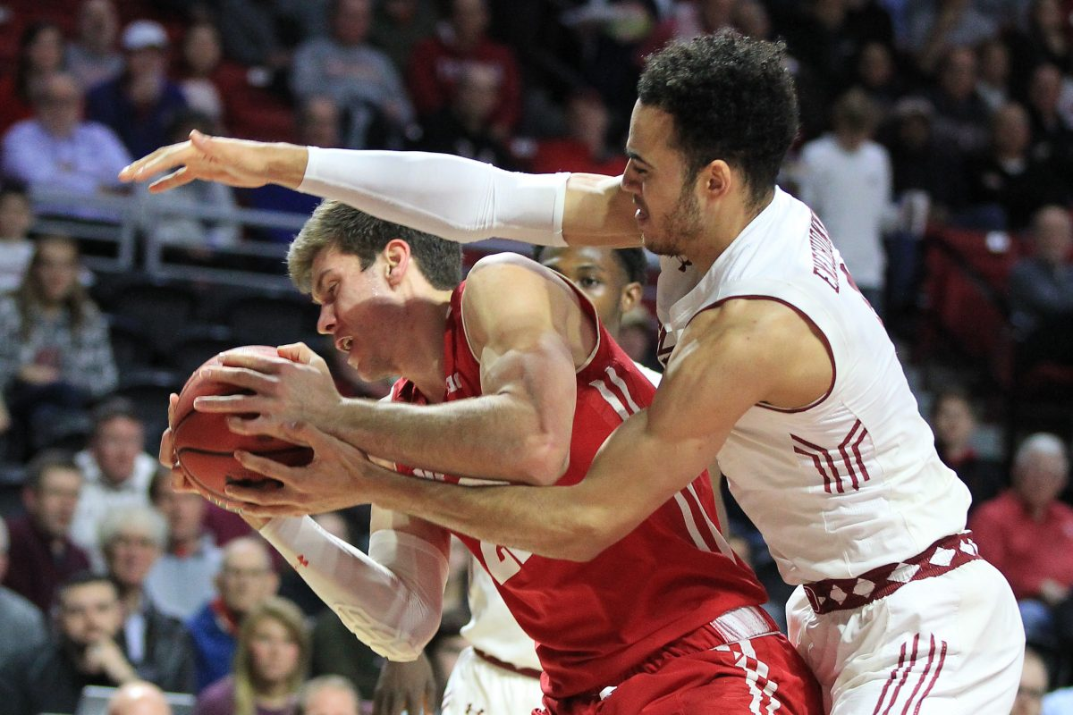 Wisconsin star Ethan Happ  (left)  fights for a rebound with Obi Enechionyia of Temple in the first half.