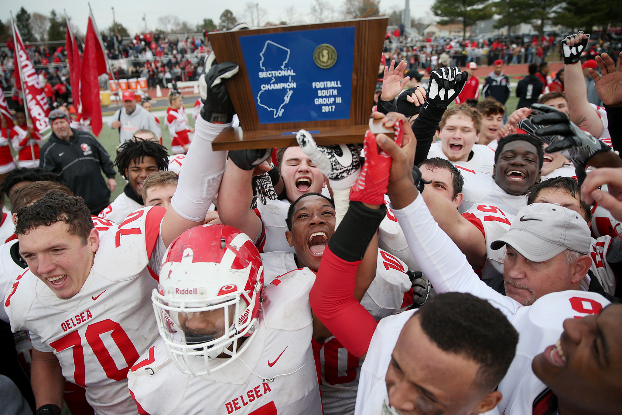 Delsea players celebrate with the South Jersey Group 3 championship trophy after defeating Woodrow Wilson.
