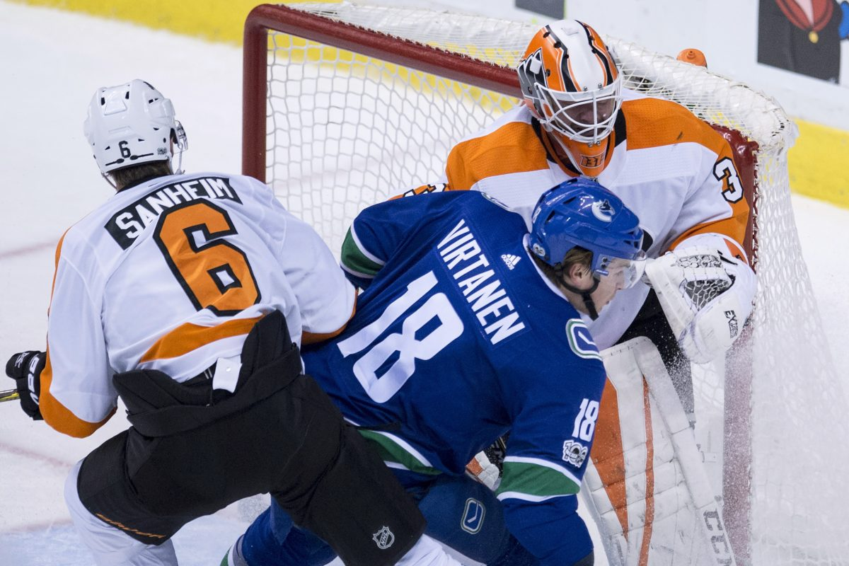 Flyers defenseman Travis Sanheim (6) tries to clear  Canucks right winger Jake Virtanen (18) from in front of goalie Brian Elliott during the second period Thursday.