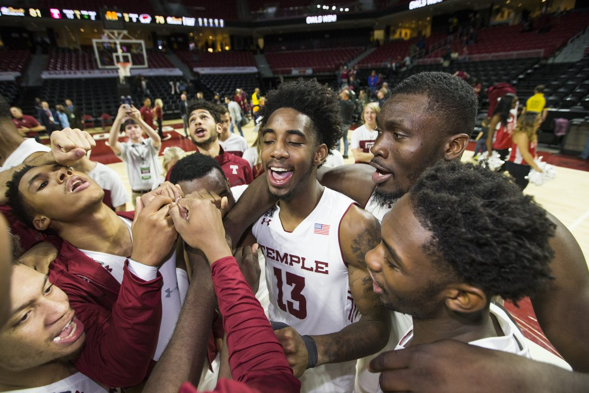 Temple players, including Quinton Rose (center), celebrate after their victory over St. Joseph's.