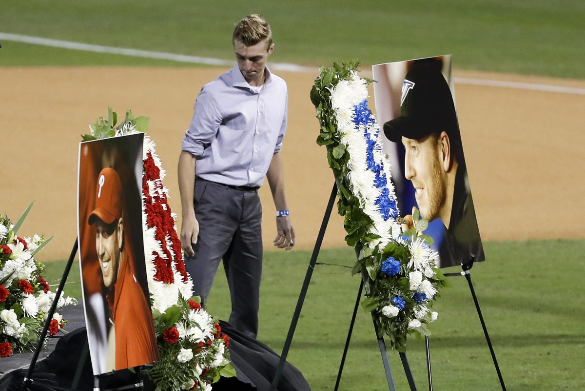 Braden Halladay, oldest son of late MLB pitcher Roy Halladay, looks at photograph of his father after a Celebration of Life for Roy Halladay at Spectrum Field in Clearwater, Fla., where the Halladay family lives.
