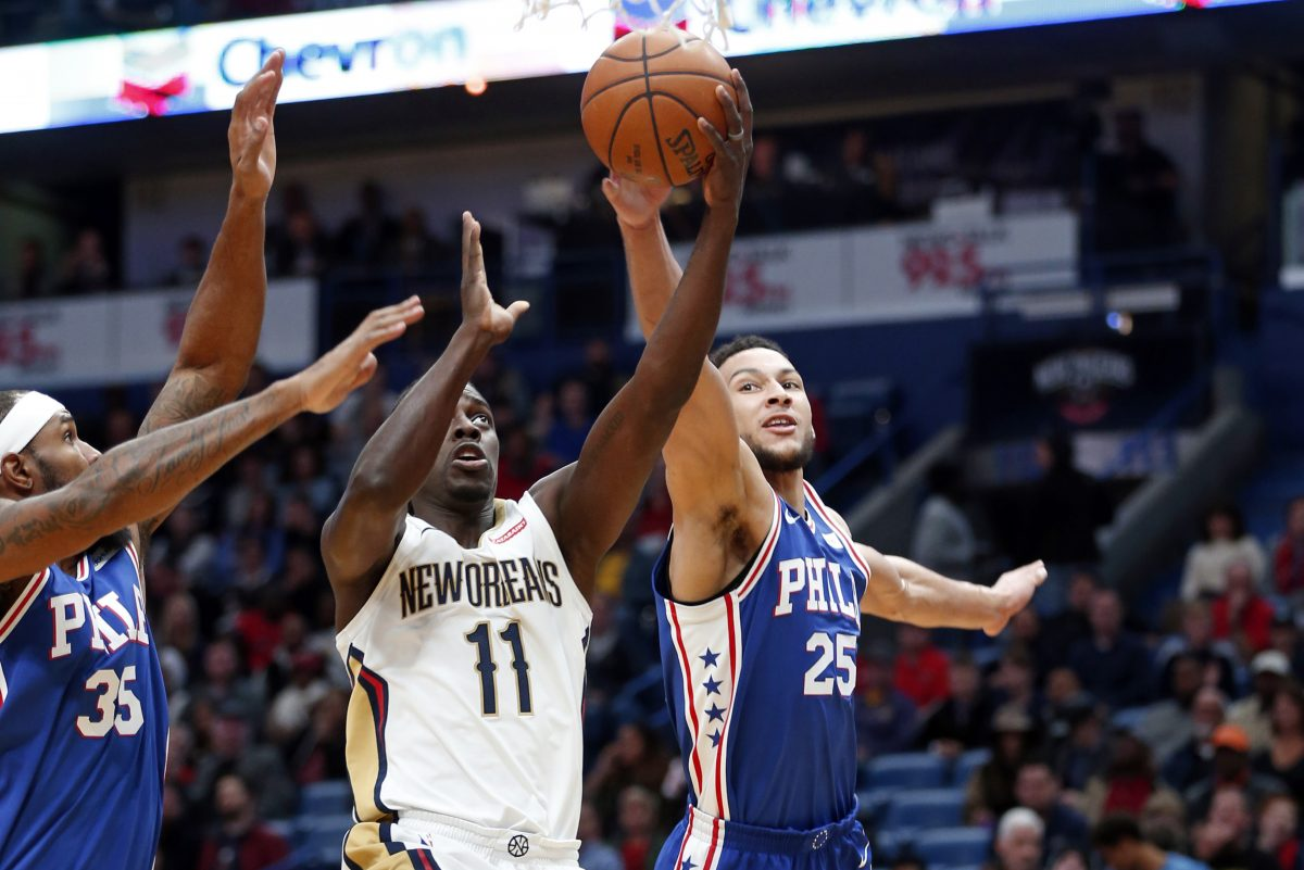 Pelicans guard Jrue Holiday (11) goes to the basket between 76ers guard Ben Simmons (25) and forward Trevor Booker in the first half.
