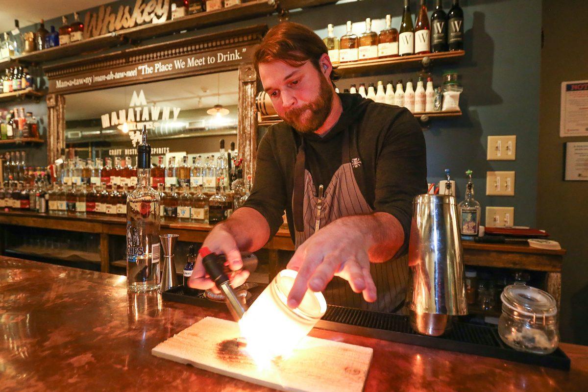 At Manatawny Craft Spirits Shop & Tasting Room, bartender Ben Spirk makes an Italian Market cocktail. Step one: Incinerate a cinnamon stick.