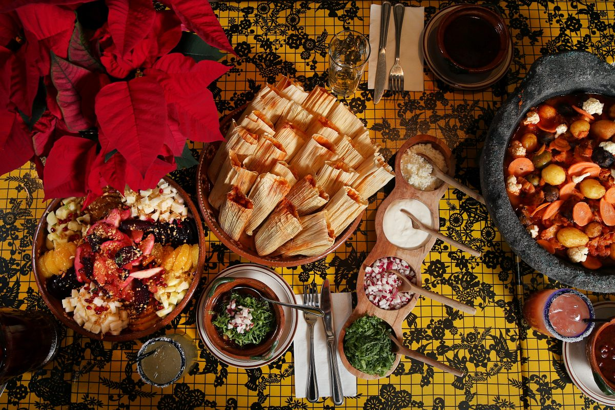 A Christmas feast, including pork pozole (bottom), ensalada de Noche Buena (Christmas Eve salad, left), chicken tamales (top) and bacalao (cod stew, right), is pictured at El Rey on Chestnut Street on Thursday, Dec. 7, 2017. TIM TAI / Staff Photographer