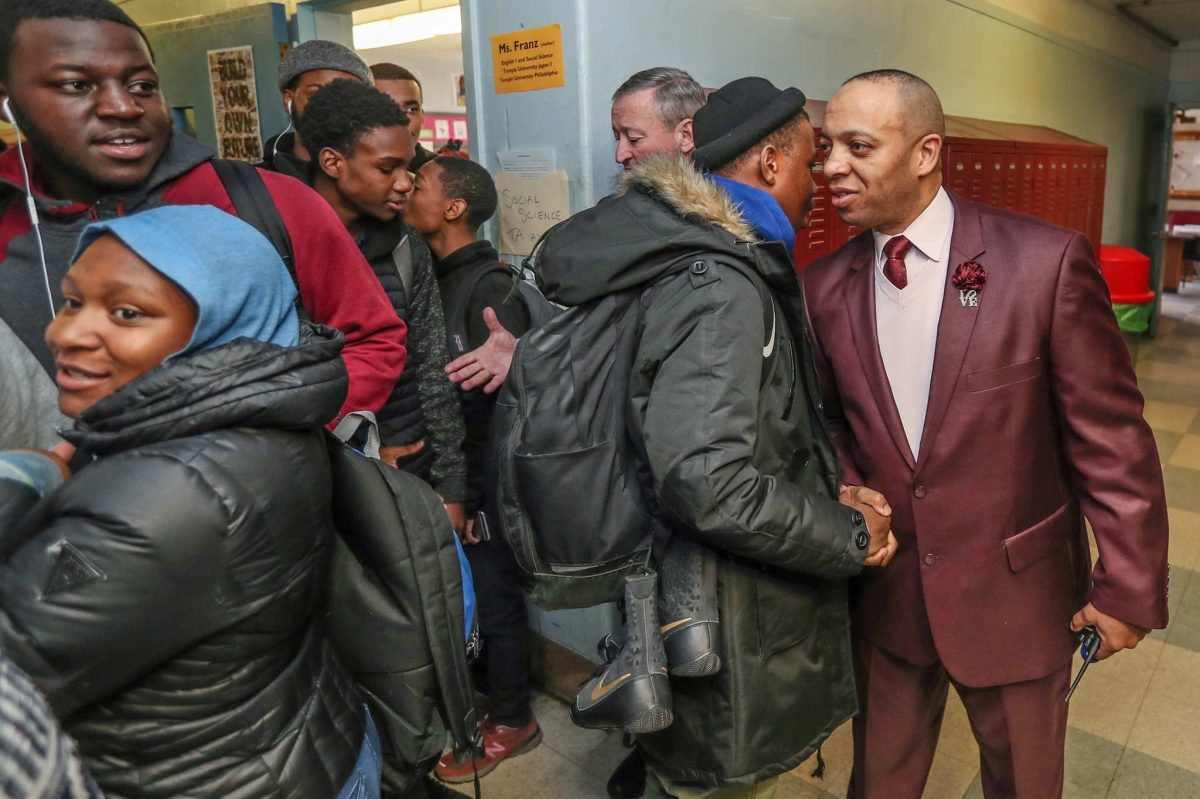 Richard Gordon IV (right), principal of Paul Robeson High School, greets one of his students during a class change while Mayor Kenney visits on Tuesday.<br />